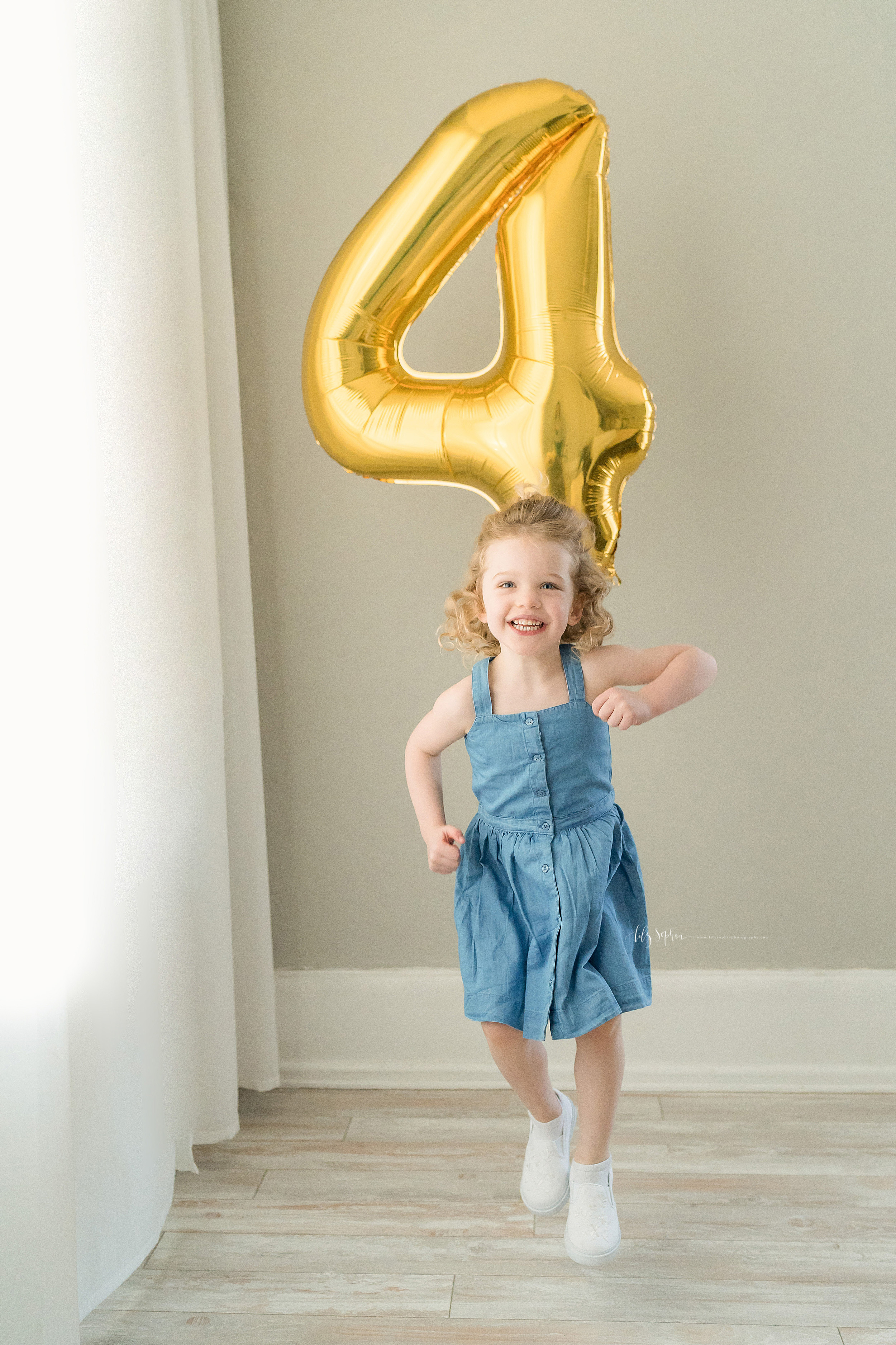 Milestone photo of a happy red-headed Atlanta four year old girl running in a natural light studio while holding a gold number four balloon.