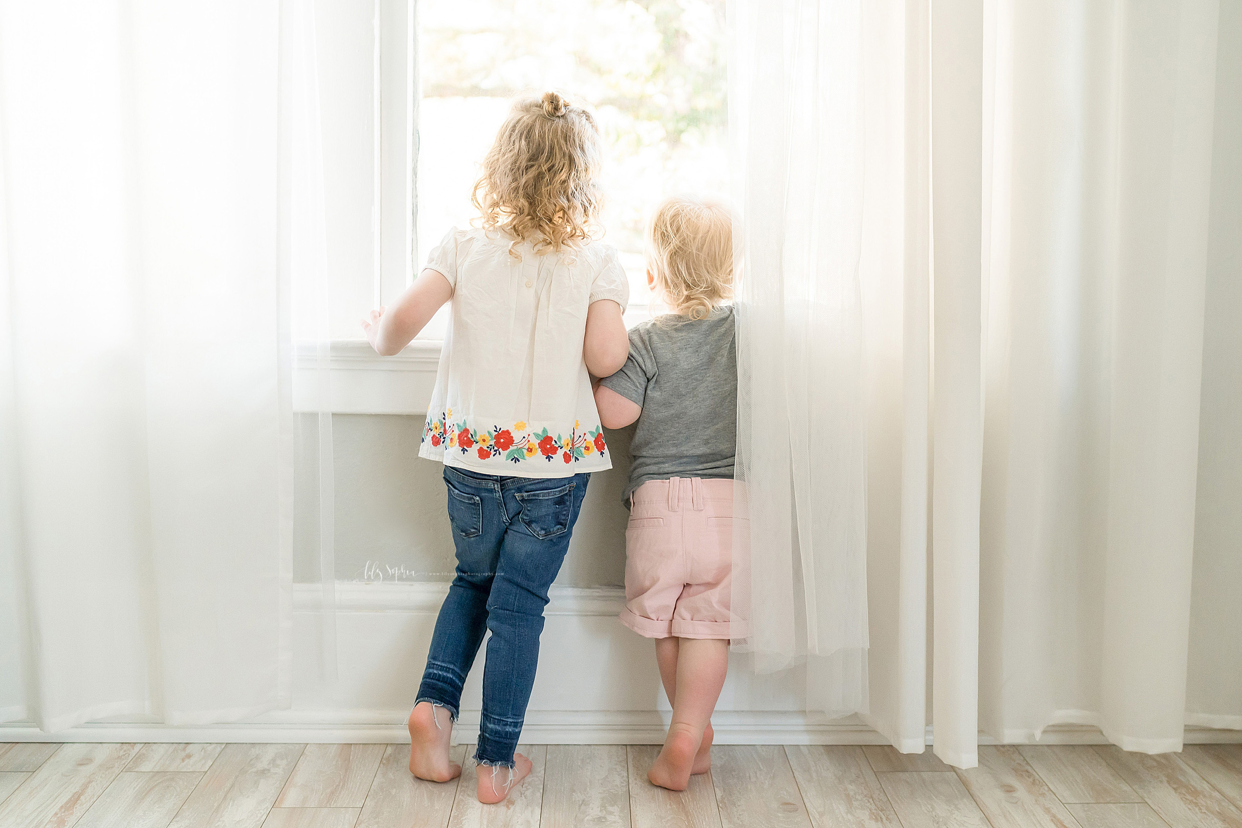 Family photo of siblings looking out a window taken by Lily Sophia Photography in an Atlanta natural light studio.