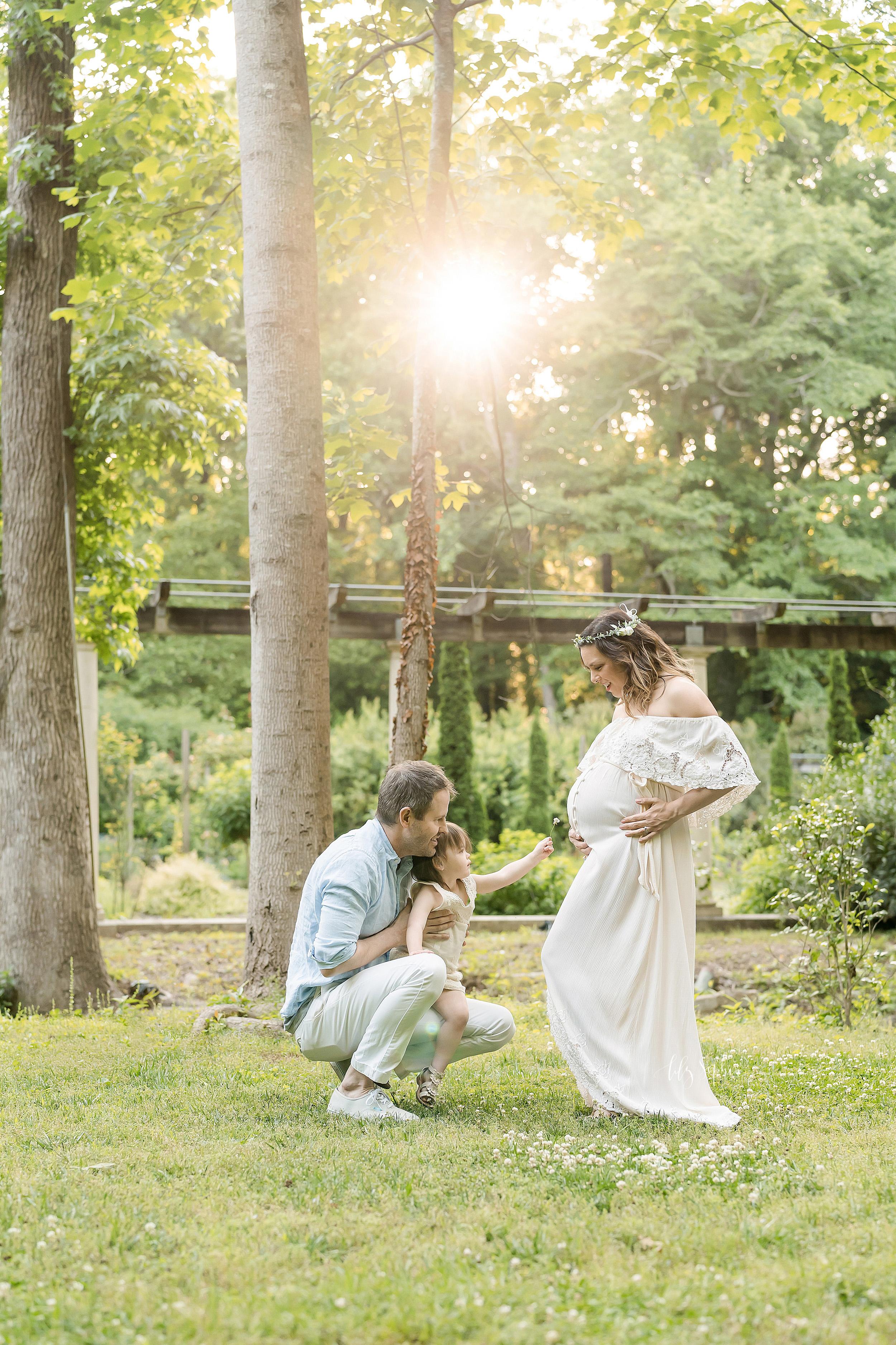 Family photo of three interacting at sunset in an Atlanta garden.