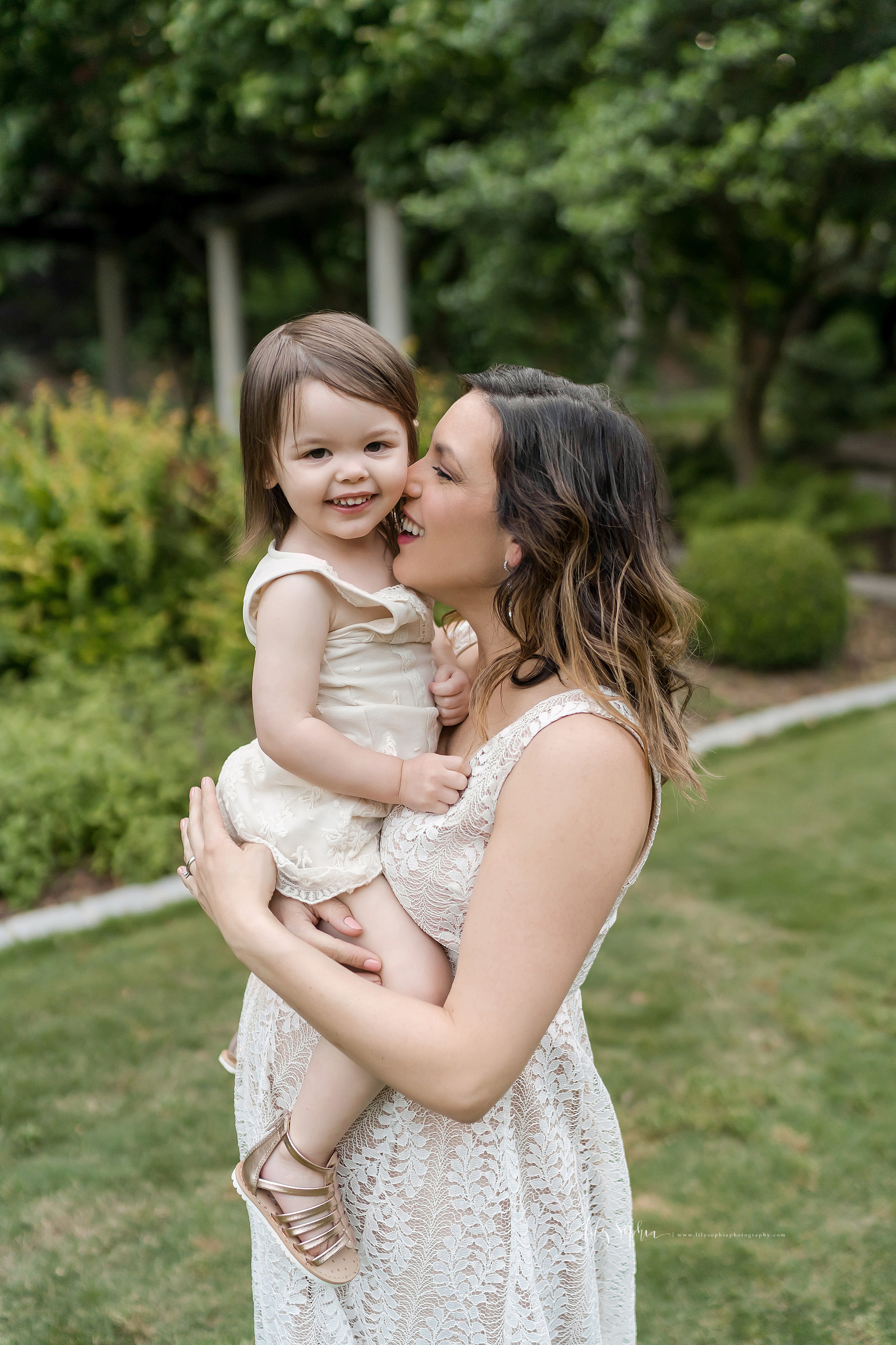 Maternity photo of a happy mother holding her toddler daughter in an Atlanta garden.