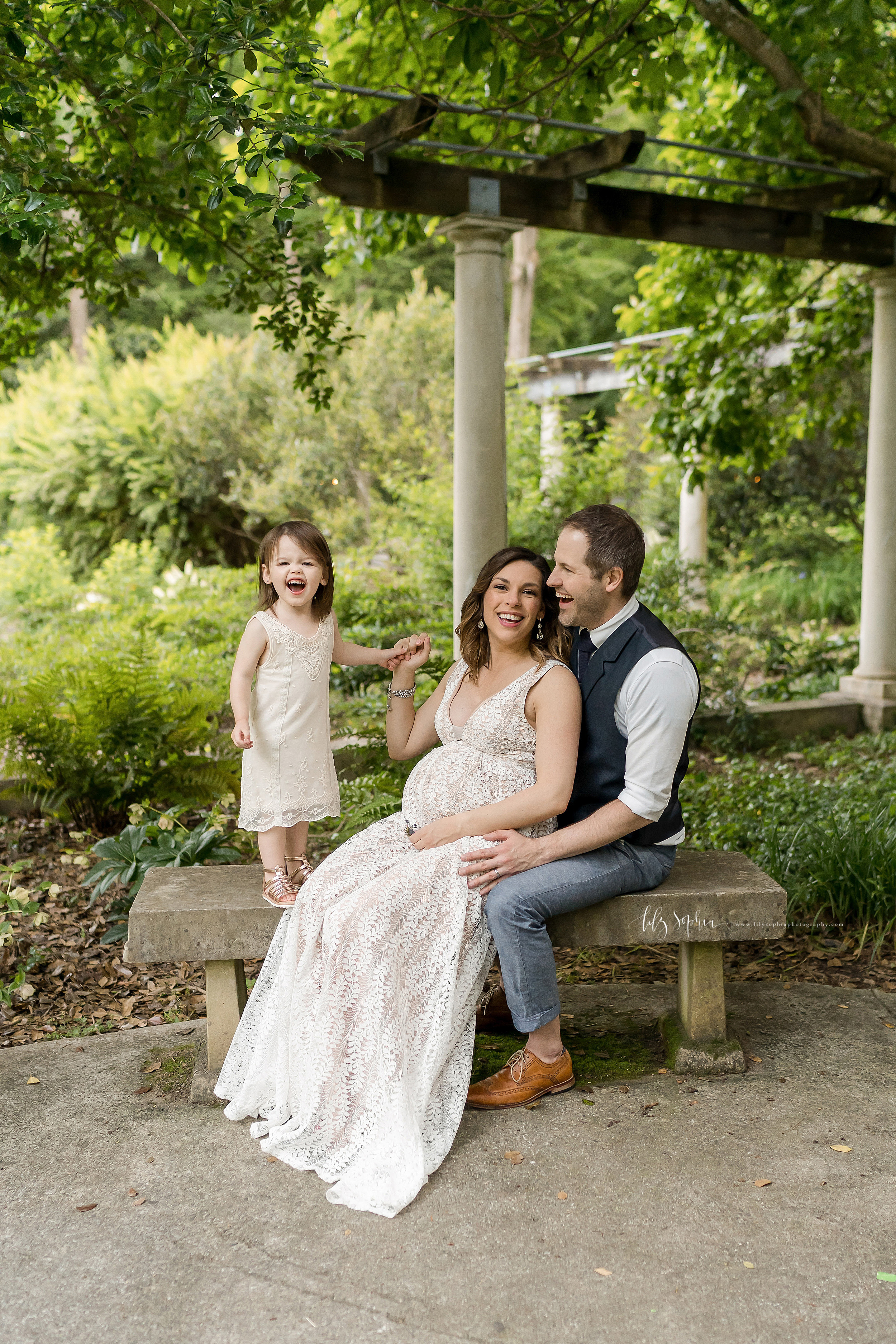 Family photo of a pregnant mom sitting on a stone bench in an Atlanta garden with her back against her husband's chest and her laughing young daughter stands next to her on top of the bench as she holds her hand.