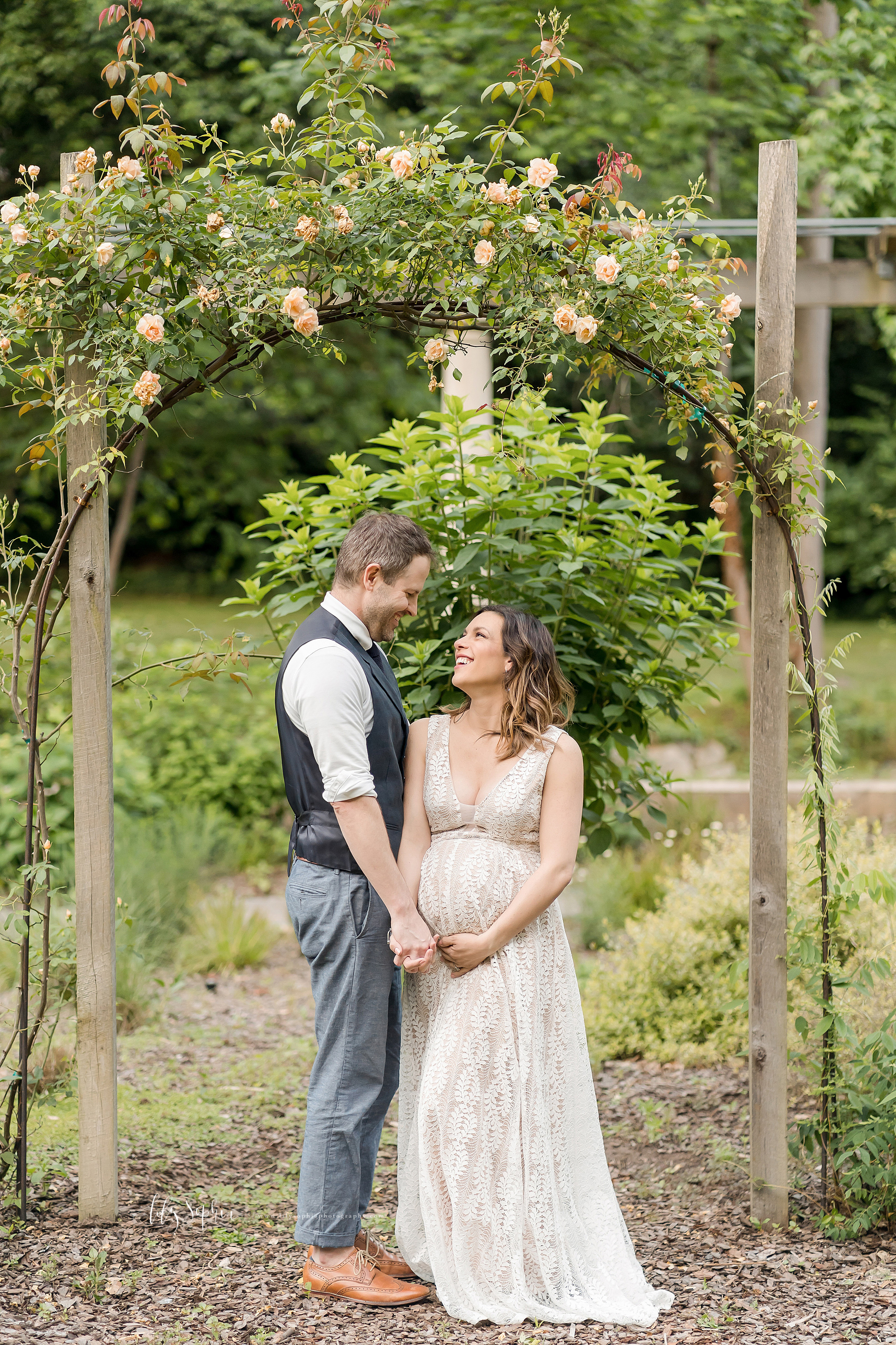 Photo of a pregnant wife with her husband standing and holding hands under an arbor in a garden in Atlanta.
