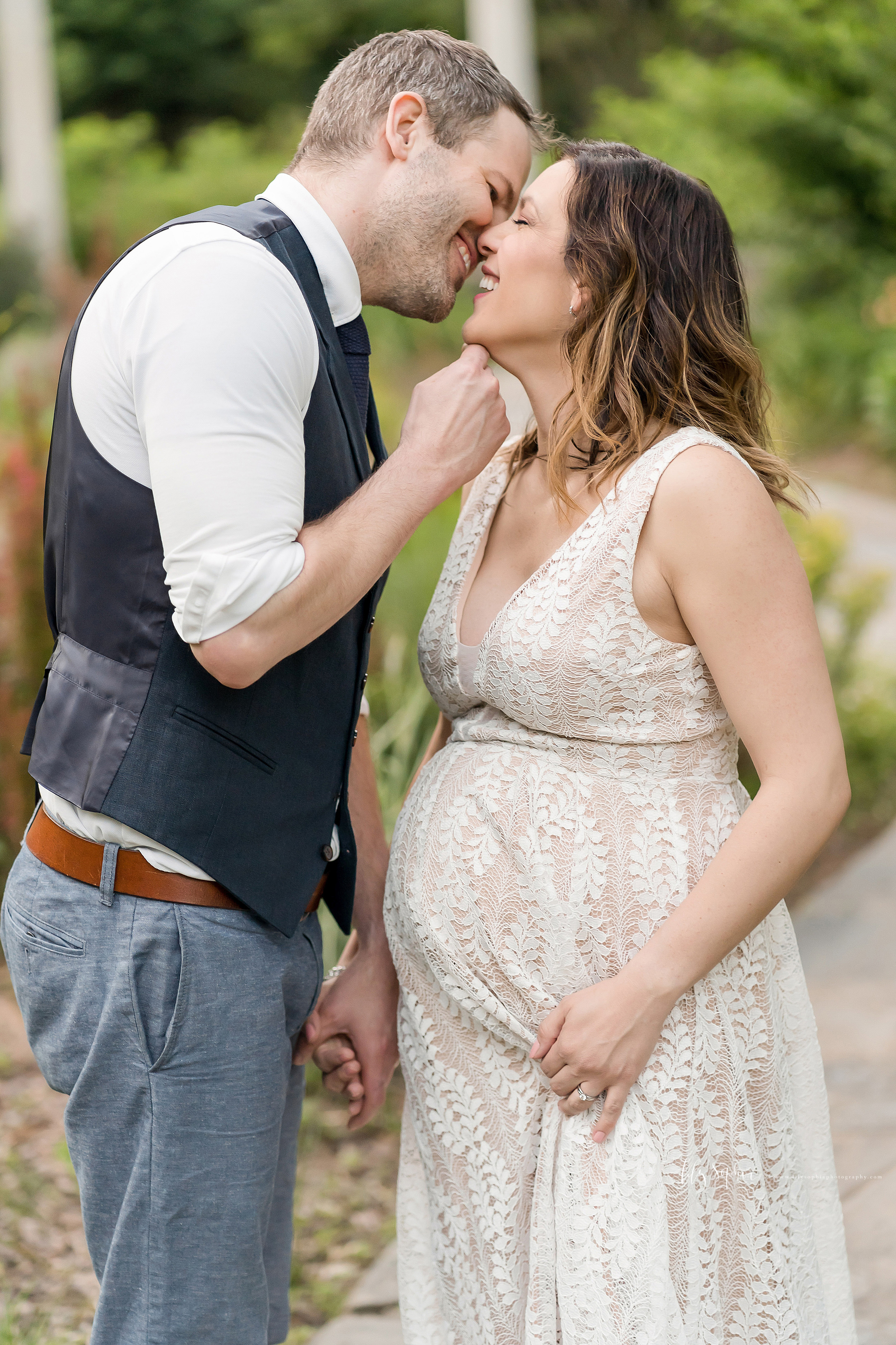 Maternity photo of a smiling husband and wife ready to kiss one another in a garden in Atlanta.