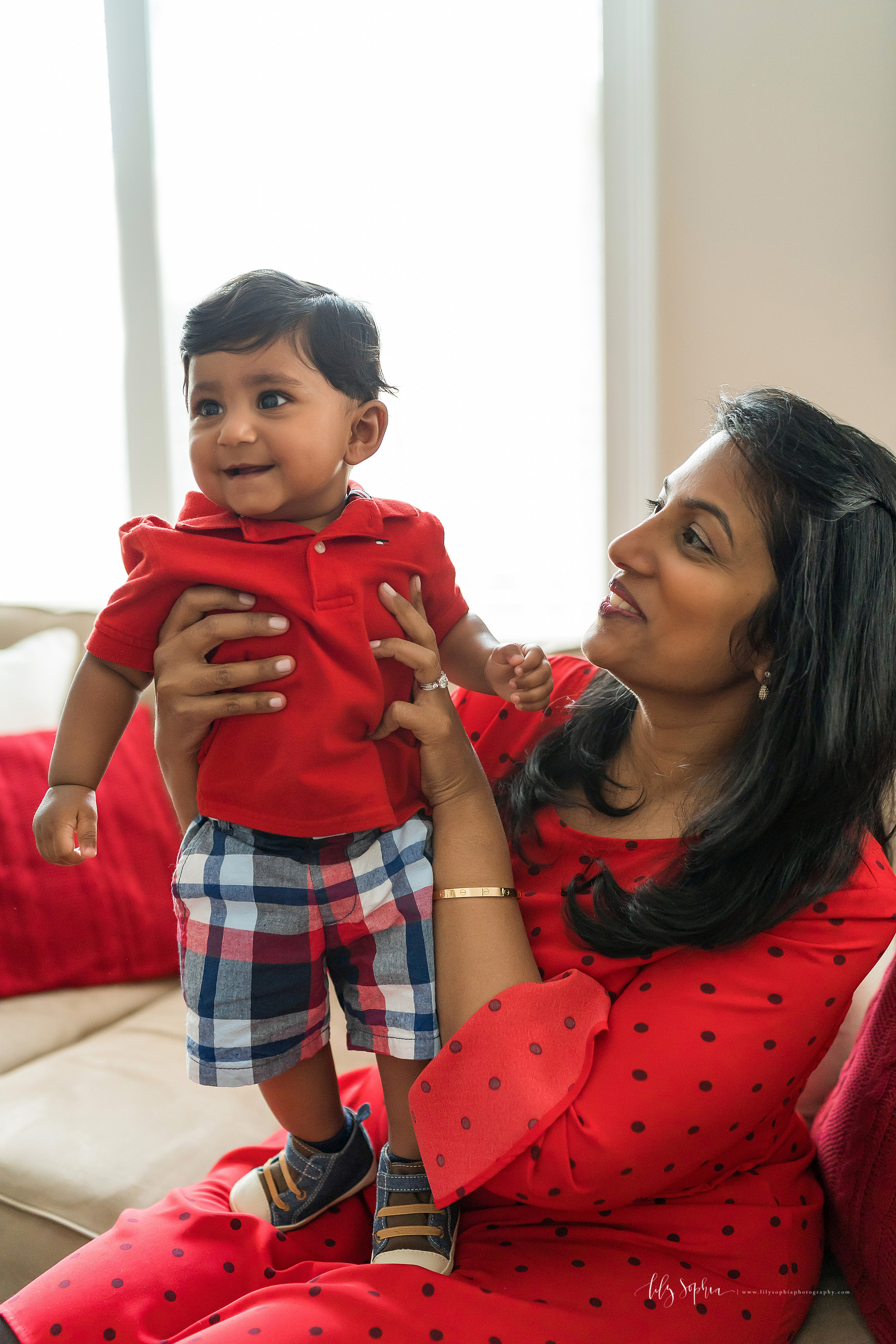 Lifestyle photo of an Indian little boy as he stands on his mother's lap in his home in East Cobb, GA.