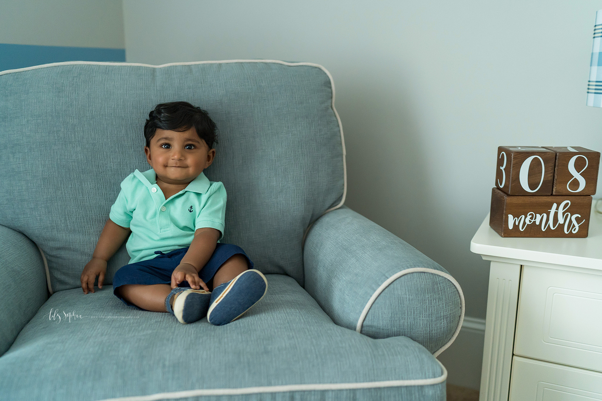 Milestone photo of an eight month old as he sits in a big blue chair in his nursery at home in East Cobb, GA.