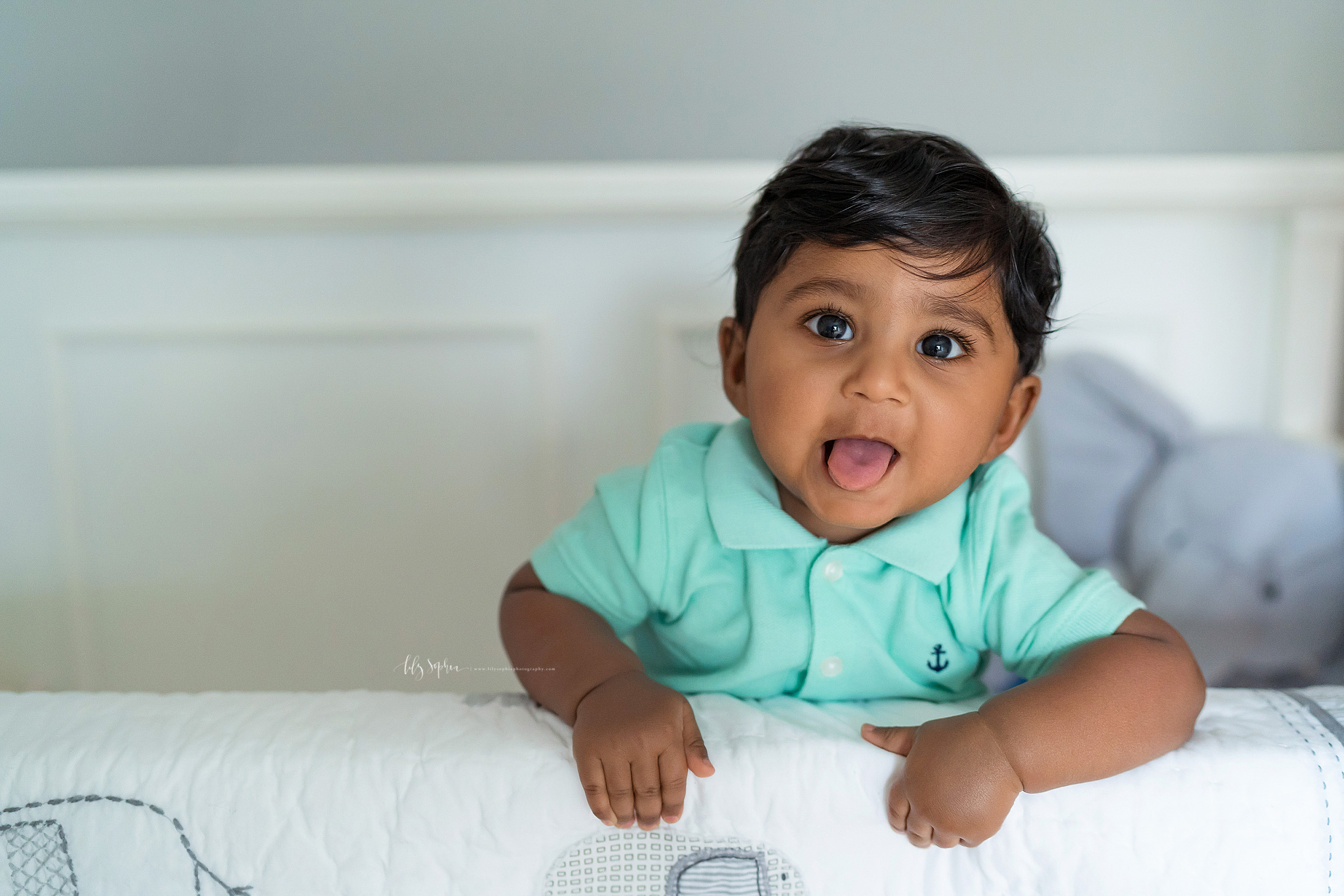 Milestone photo of an Indian eight month old as he stands in his crib in his home in East Cobb, GA.