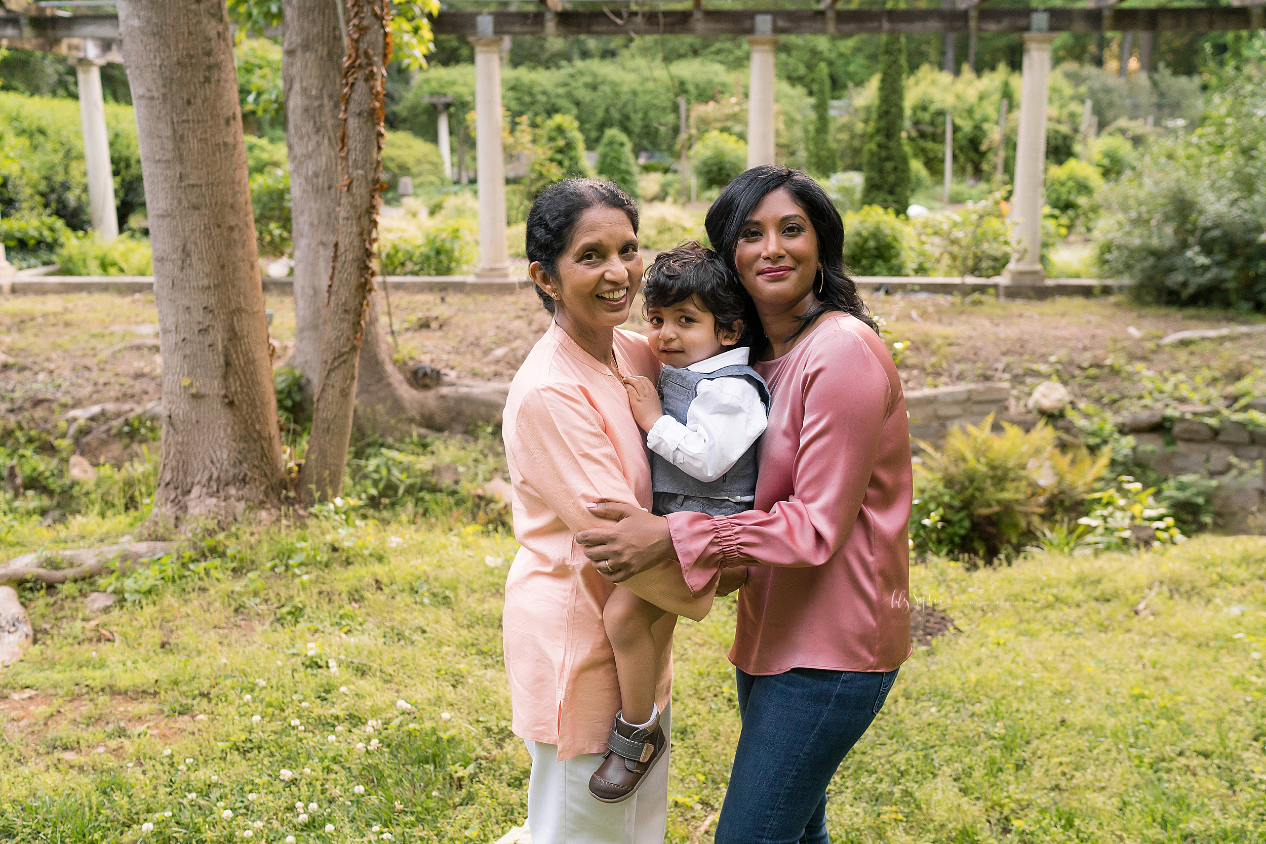 Generational photo of an Indian grandmother, daughter, and her toddler son at sunset in a garden in Atlanta.