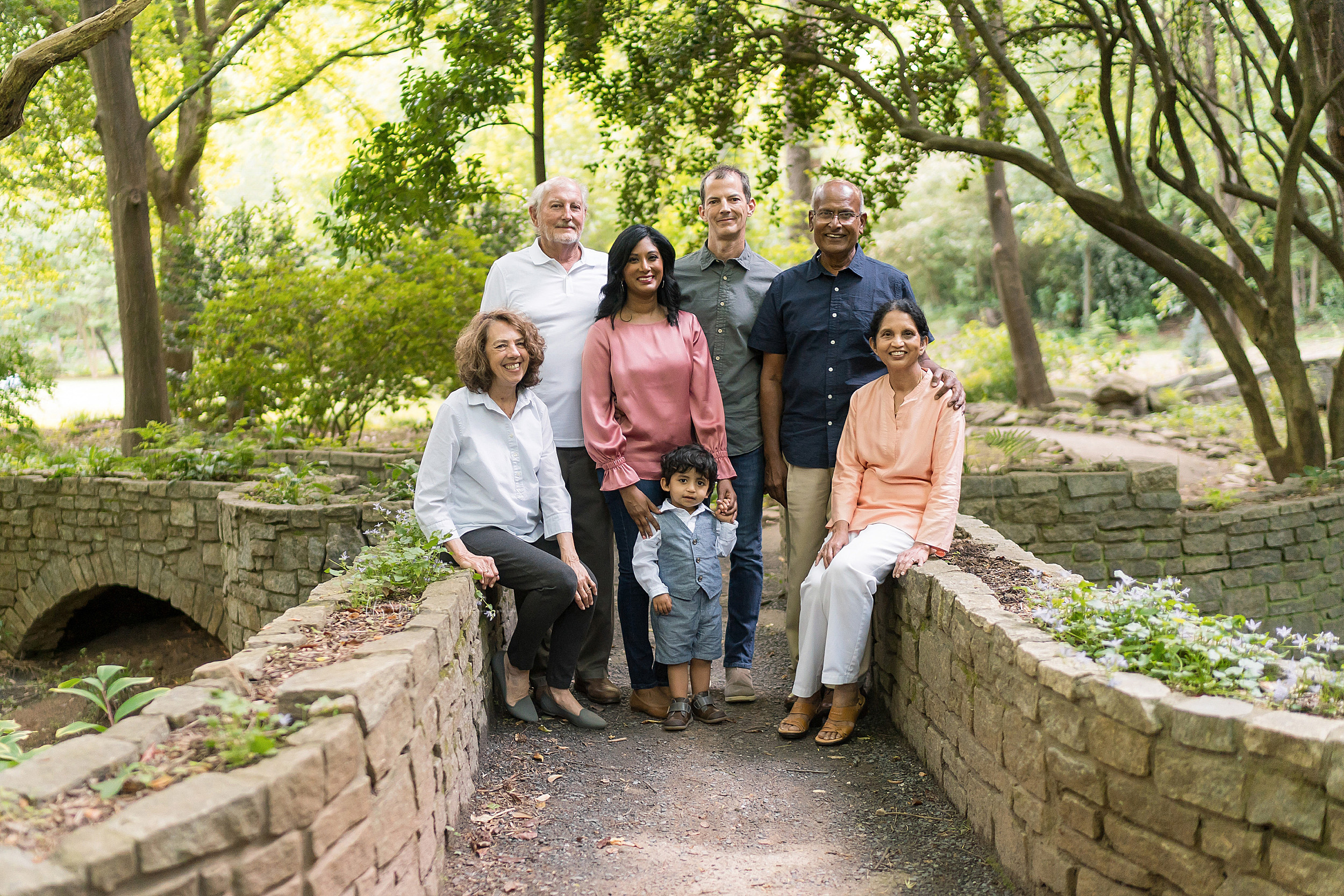 Family photo of seven with mom, dad, two-year old son, and both sets of grandparents on a stone bridge in a garden at sunset in Atlanta.