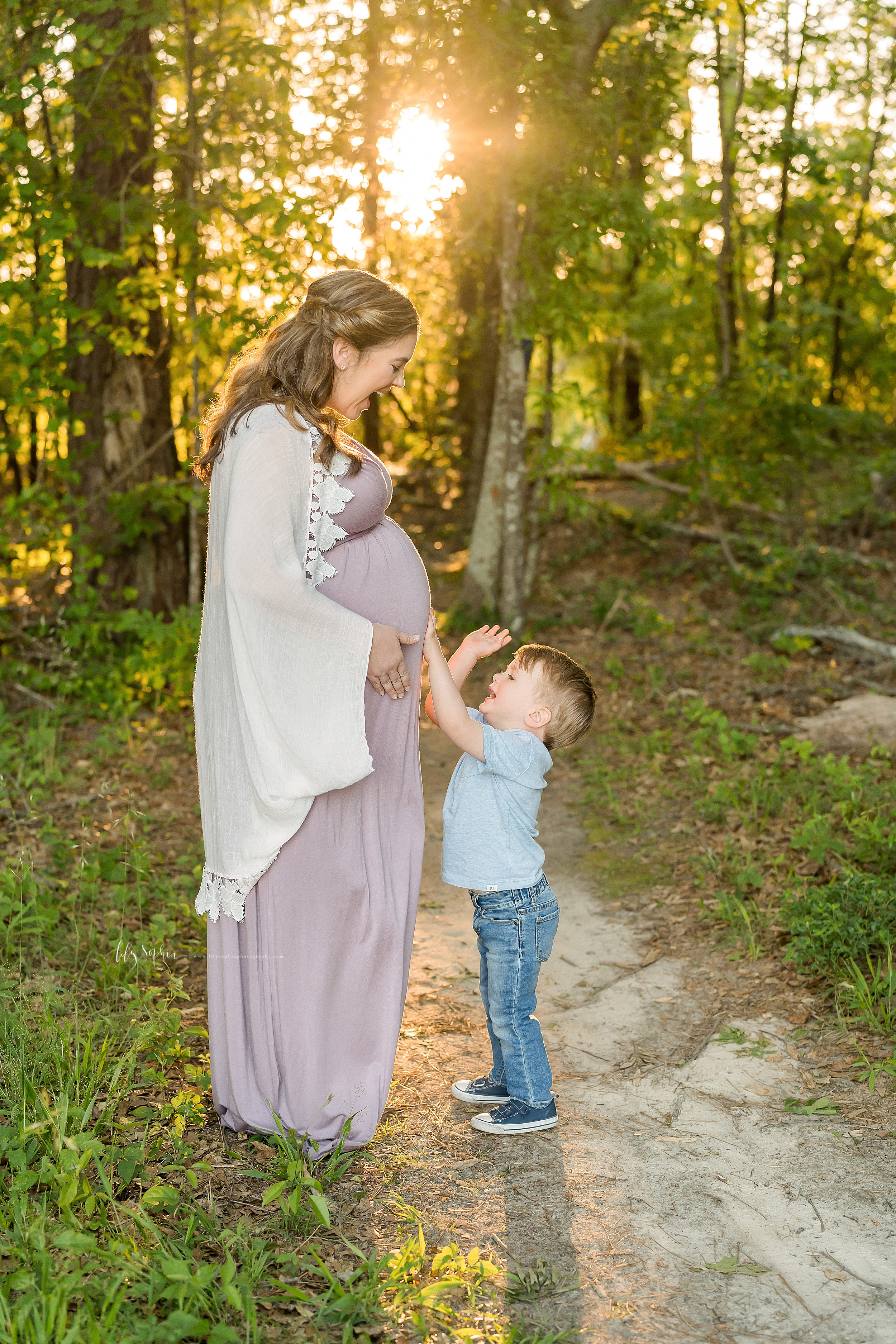 Family photo of a happy mother and toddler son in the woods on a mountain in Atlanta as he plays the drums on her pregnant belly.