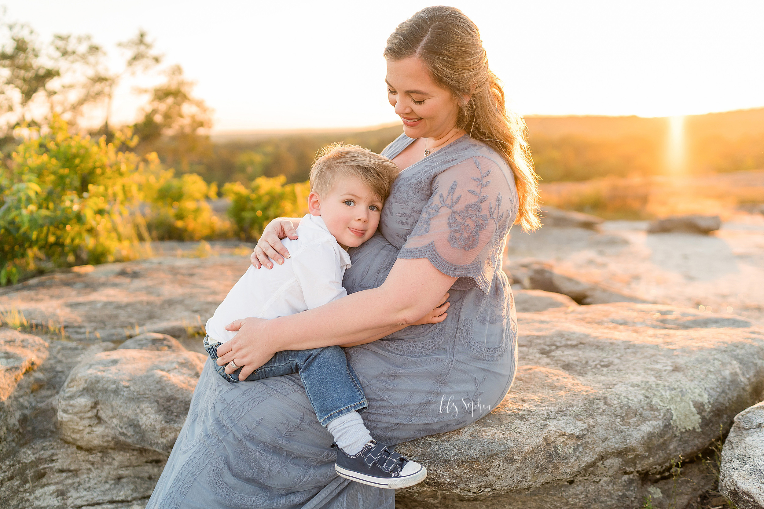 Photo of a pregnant mother holding her toddler son on her lap as she sits on a stone mountaintop near Atlanta, GA.