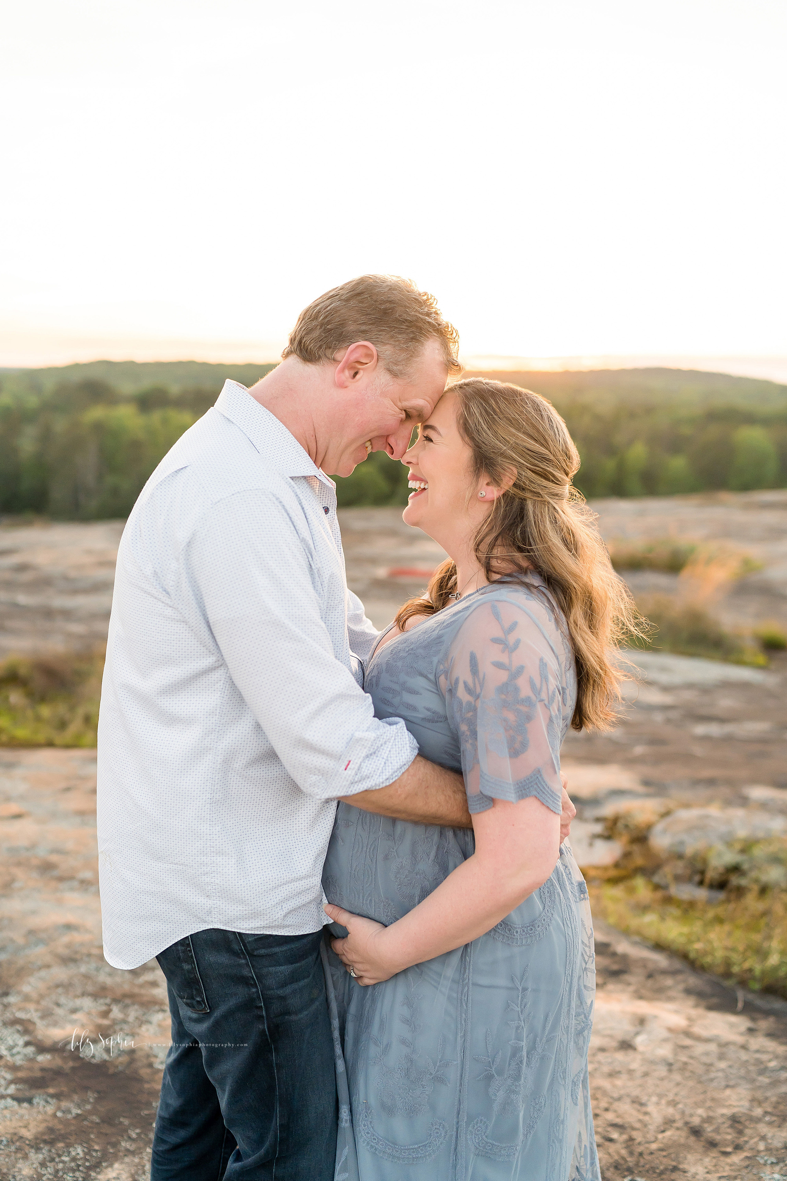 Maternity photo of an ecstatic husband and wife as they laugh with their foreheads together at the top of an Atlanta mountain at sunset.