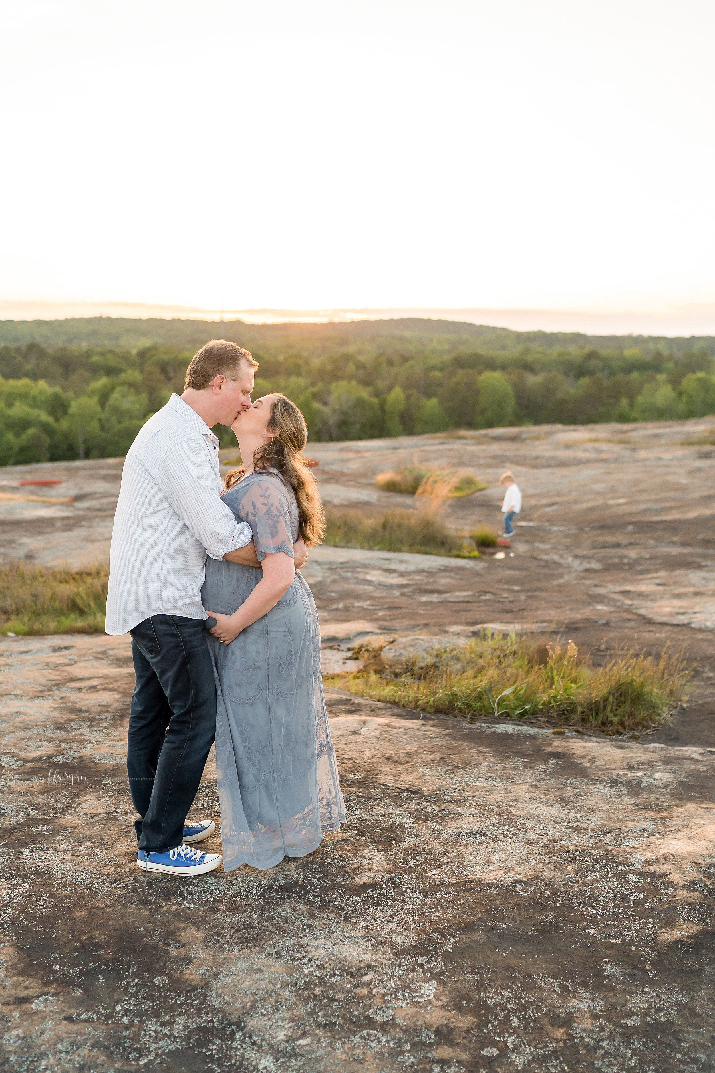 The love between a husband and pregnant wife is captured as they embrace and kiss on an Atlanta mountaintop with their toddler son playing in the background.