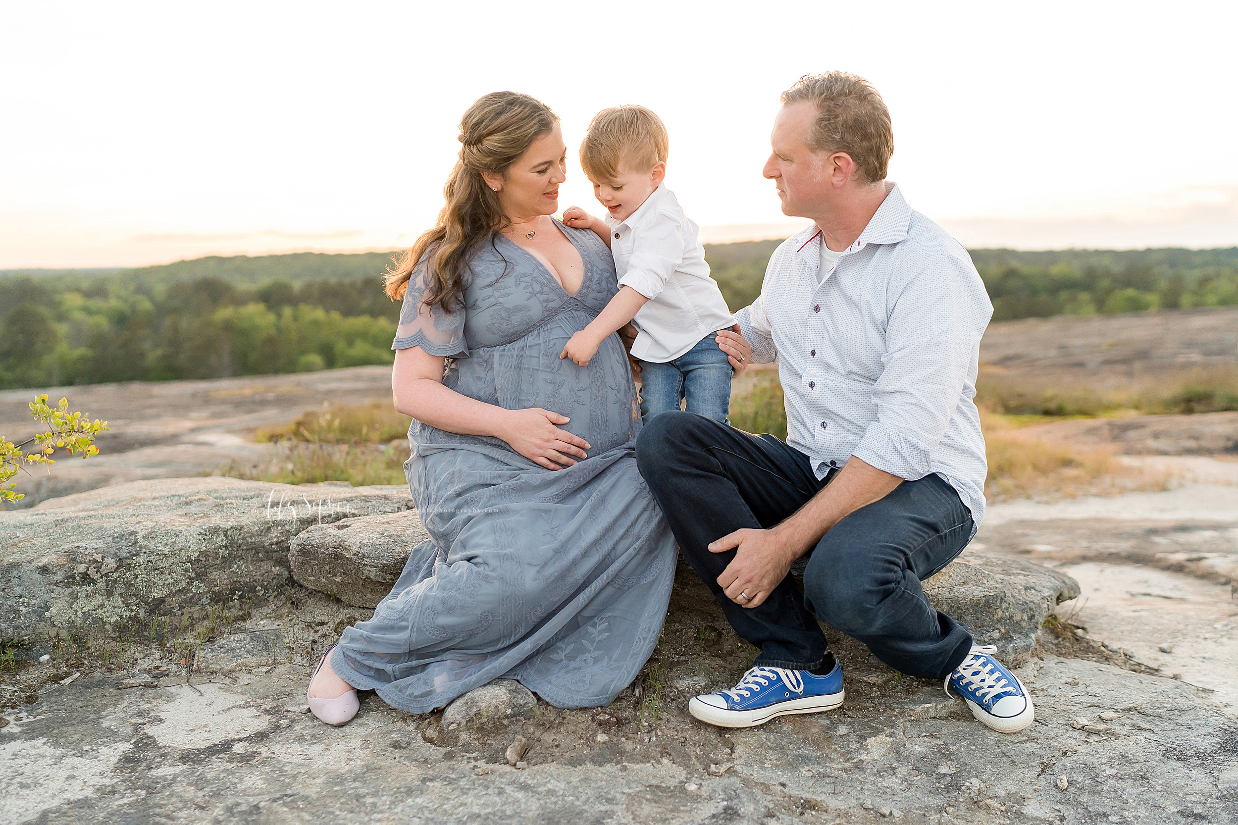 Family photo of three, soon-to-be four, on a mountaintop in Atlanta at sunset.
