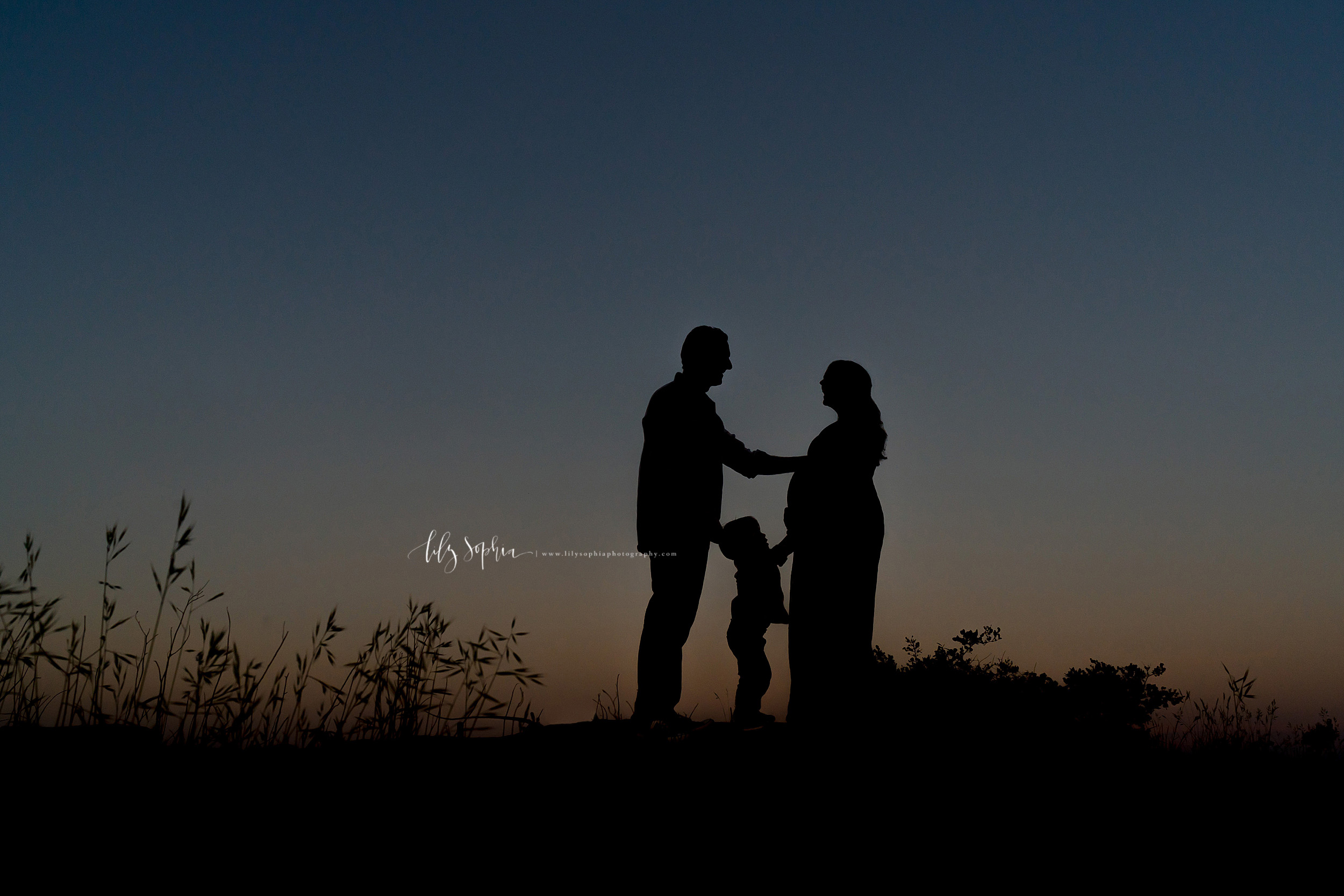 Family of three silhouetted in a maternity photo taken at sunset on a mountain in Atlanta, GA.