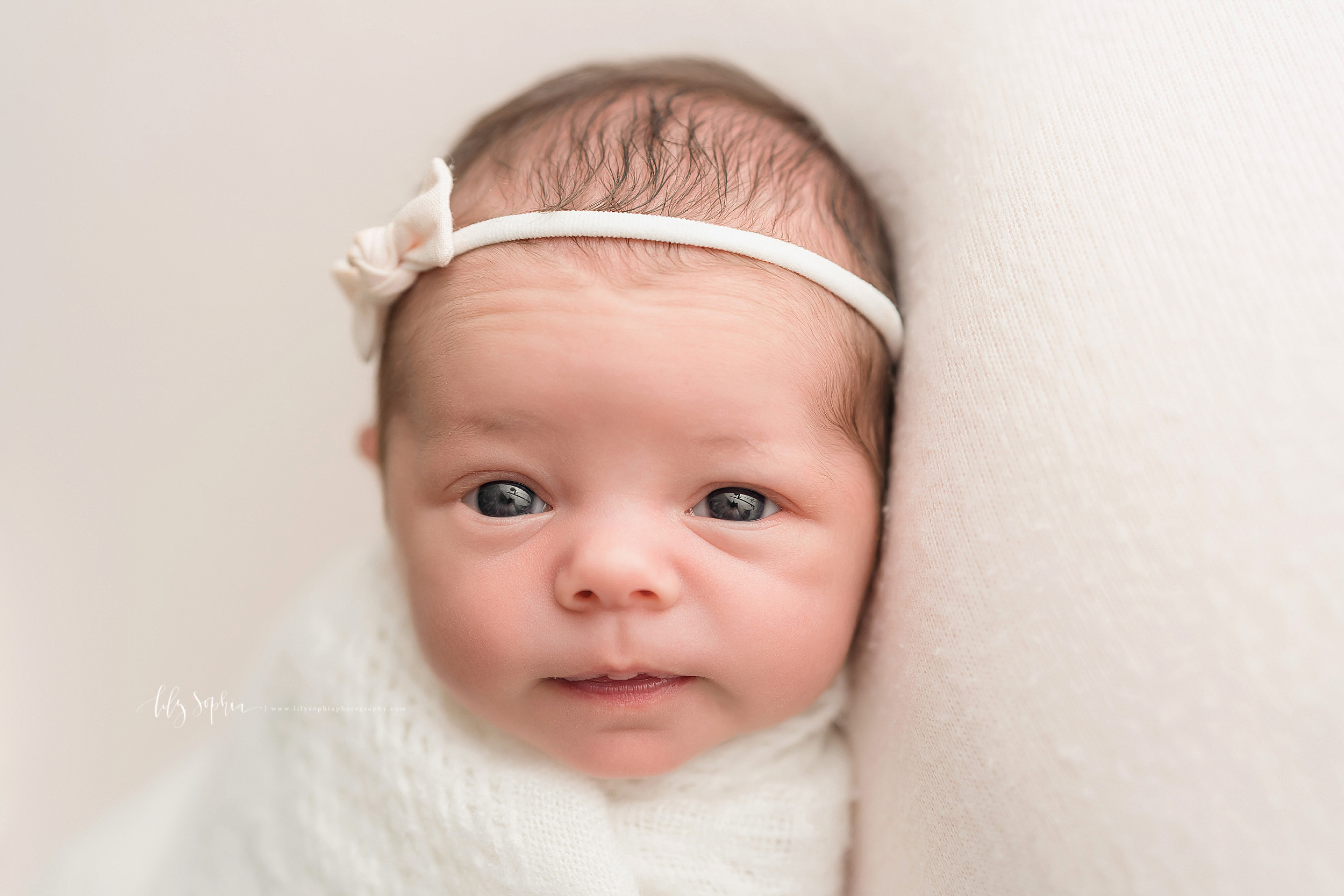 Newborn photo of a wide-eyed infant girl who is wrapped in a soft white knit blanket and is wearing a pink headband with a bow as she lays in a natural light Atlanta studio.