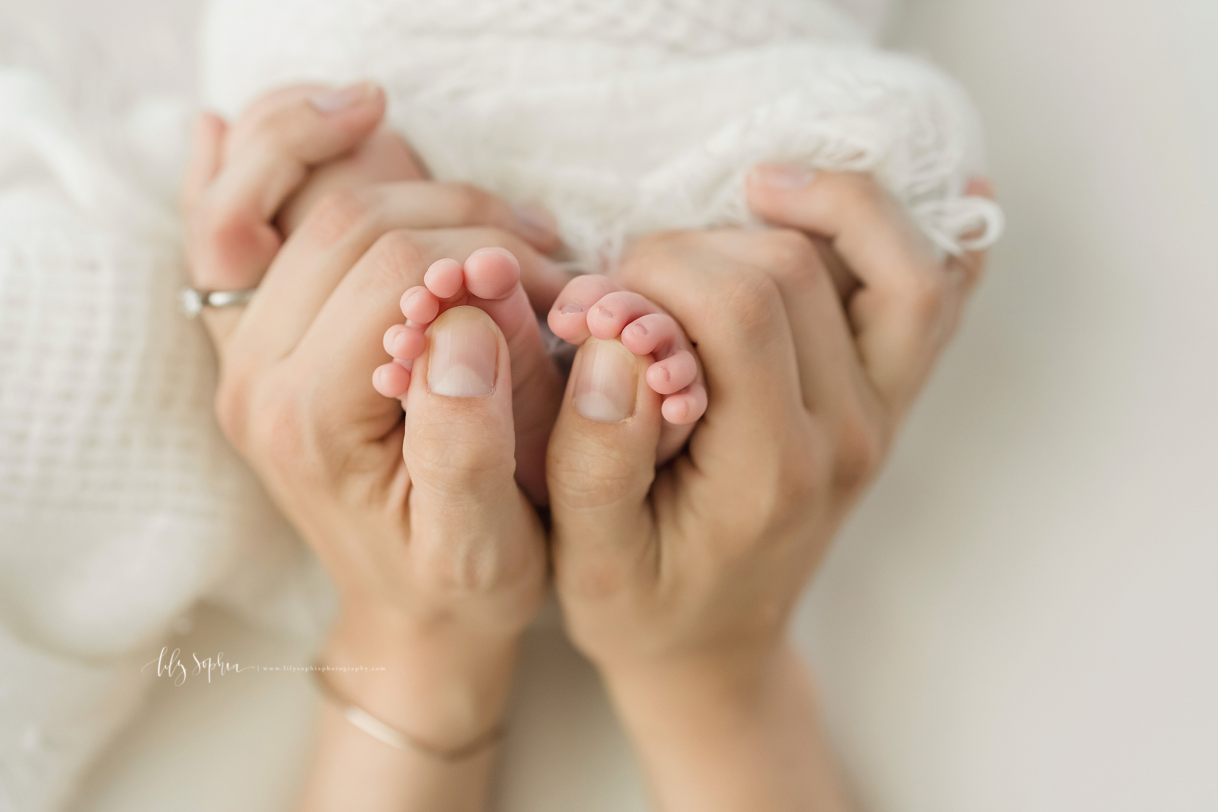 Newborn image of mom holding her infant daughter's feet and admiring the tiny toes and toe nails taken in Atlanta.
