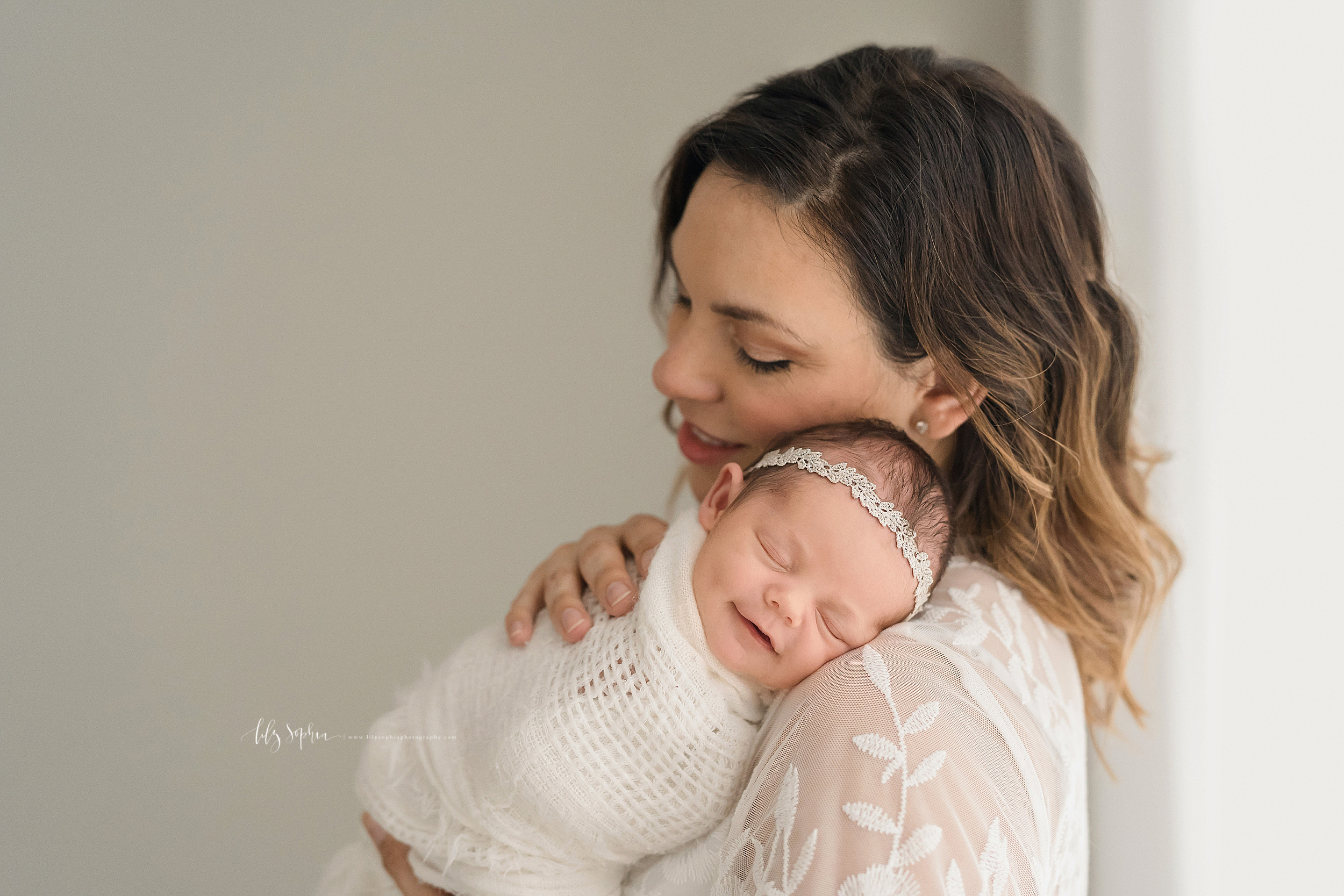 Family photo of a mother and her smiling newborn as mom holds her baby girl on her shoulder wrapped in a soft knitted blanket and stands in front of a window in a natural light studio in Atlanta.