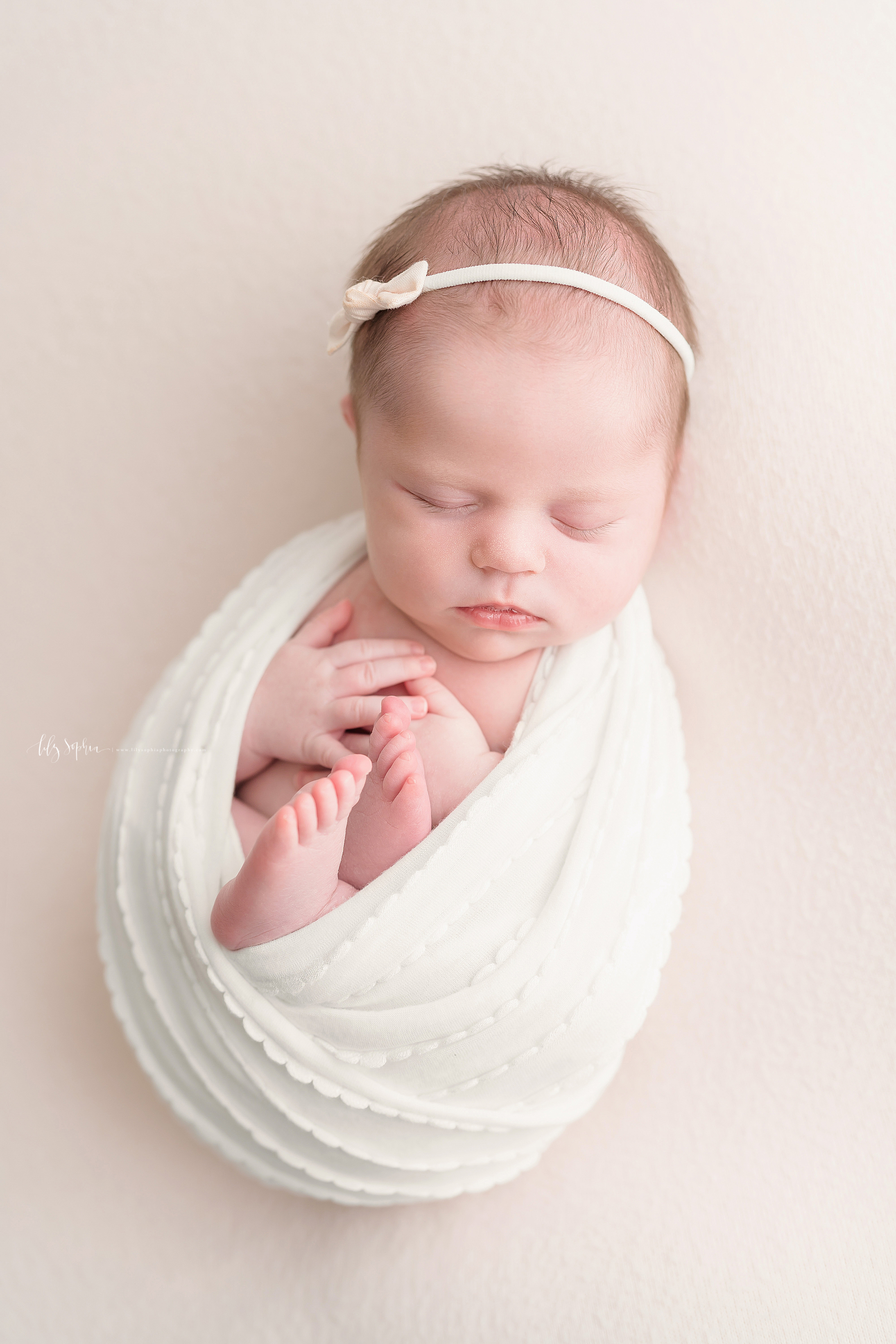 Newborn photo of a sweet sleeping baby girl wearing a cream bow headband in her brunette hair and bundled in a cream wrapped taken in a natural light studio in Atlanta, Georgia.