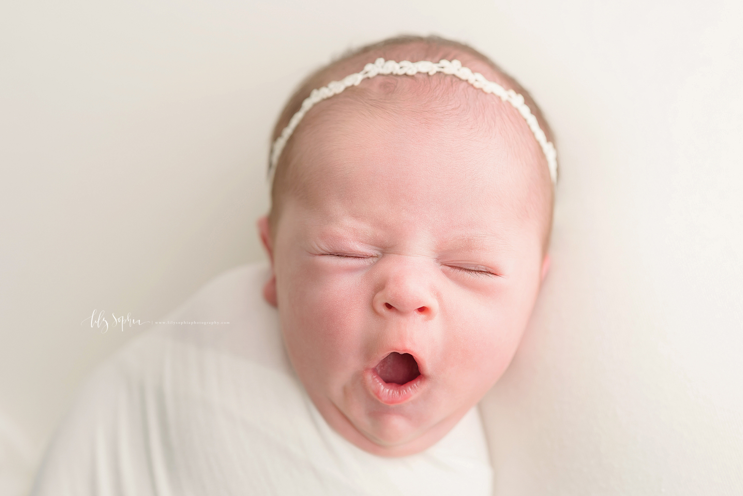 Photo of a newborn baby girl yawning for the camera in an Atlanta studio in natural light as she wears a crocheted head band and is swaddled to her neck in a blanket.