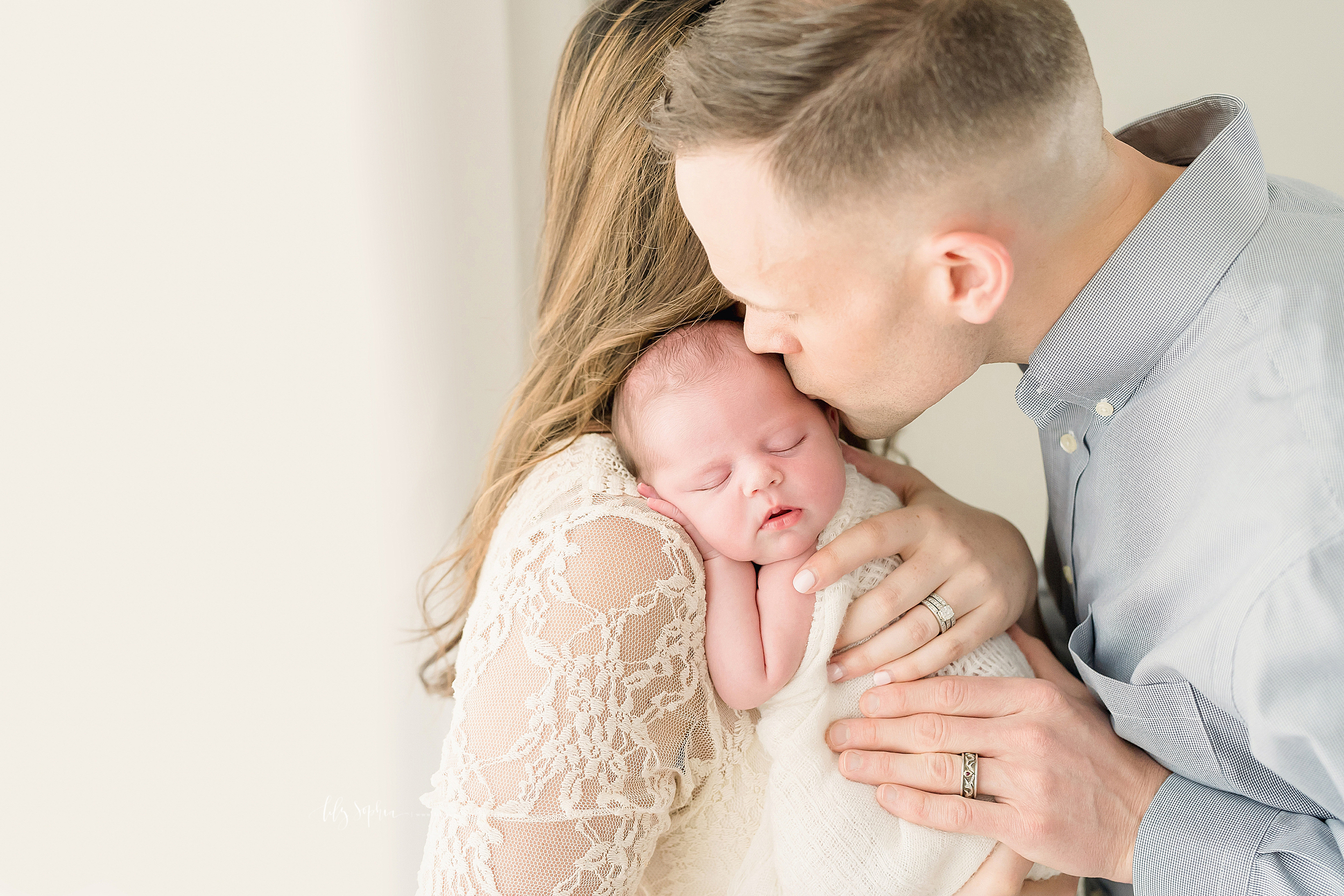 Family newborn photo of mom holding her sleeping baby girl on her shoulder as dad gently kisses her head in a natural light Atlanta studio.