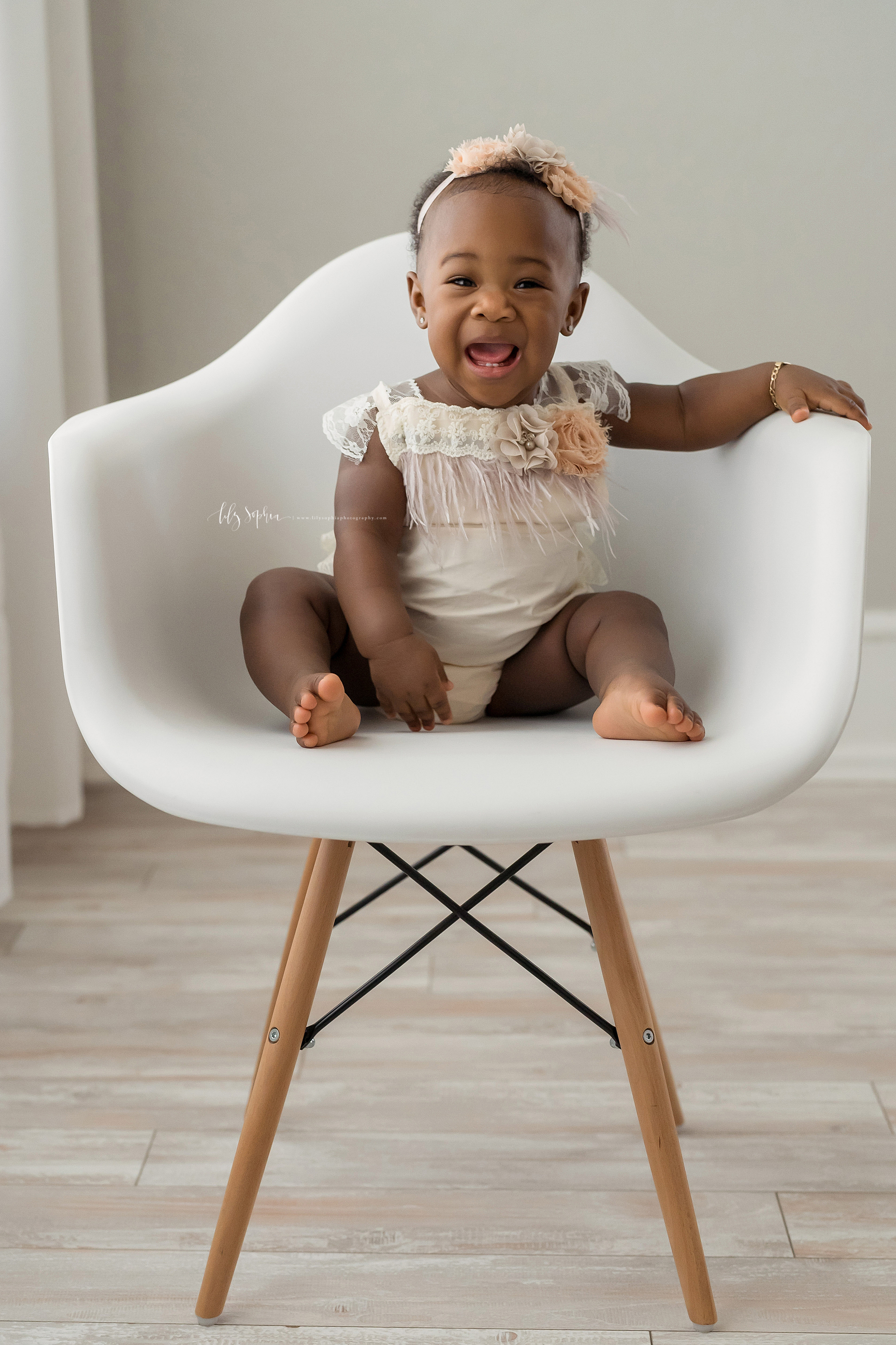 Milestone photo of an excited African-American girl who is turning one year old as she sits barefoot in an Atlanta studio in natural light on a molded white chair wearing a cream head band with peach roses and a cream one piece outfit with lace, fringe and a peach rose.