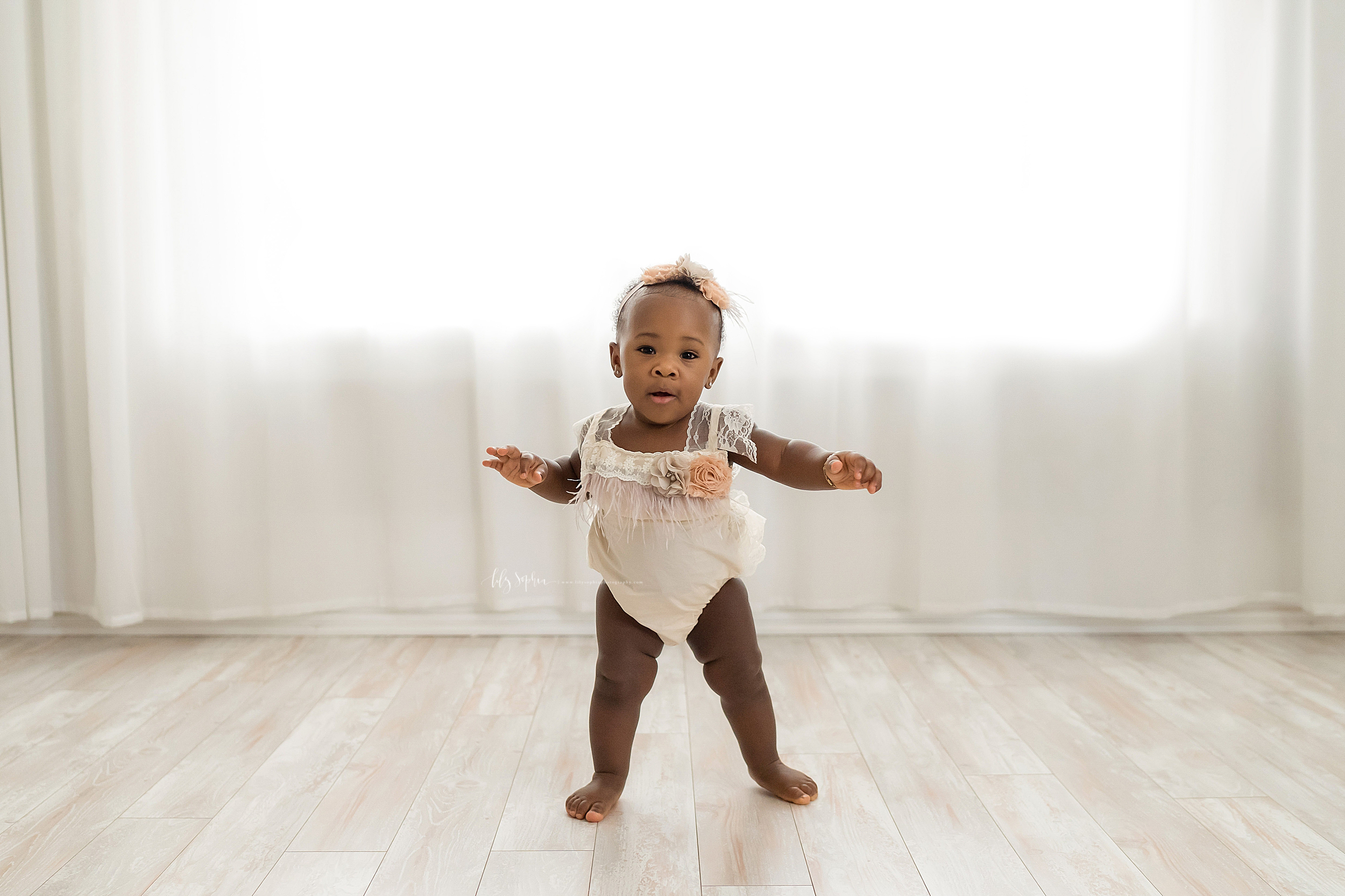 Milestone photo of an African-American one year old girl as she stands barefoot wearing a one piece cream outfit with lace, roses, and fringe and holds out her arms to help her balance in an Atlanta studio.