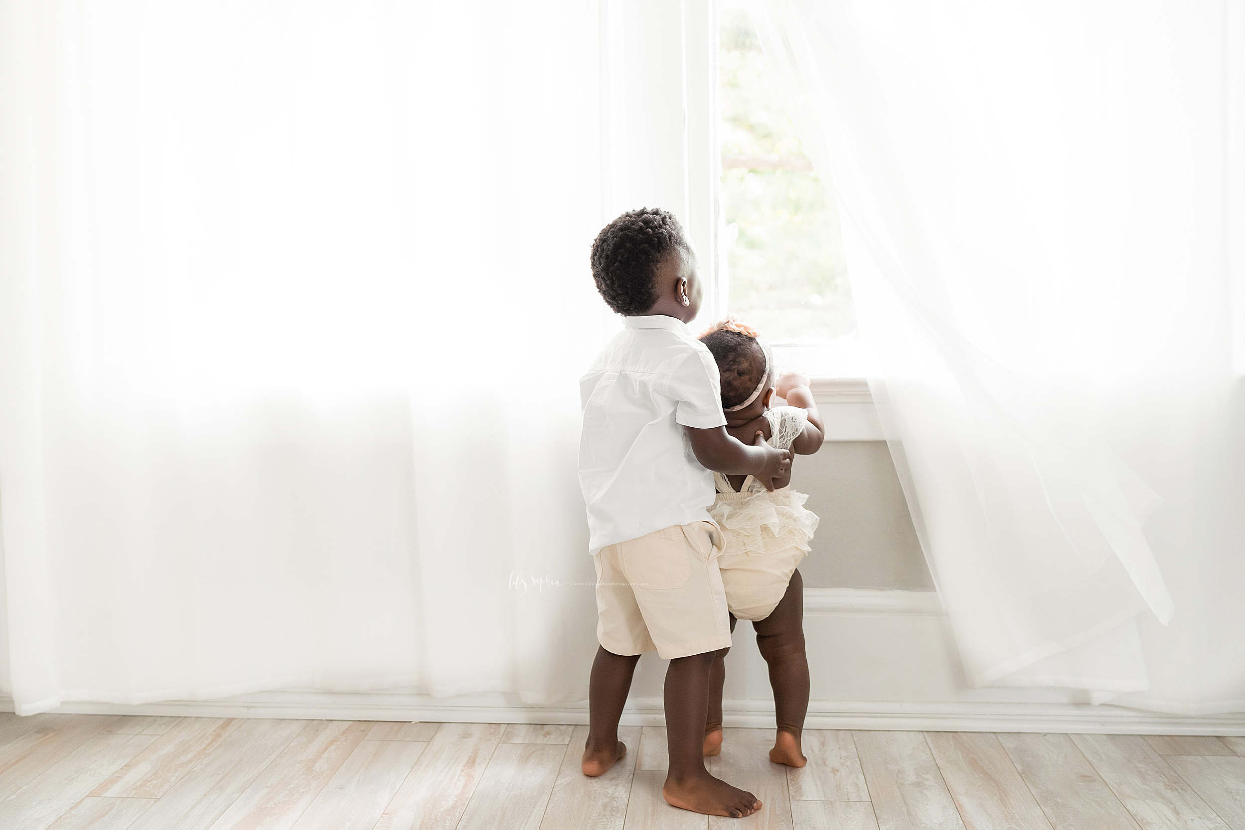 Family photo of two African-American children, a brother and sister, as they look out of a studio window in Atlanta.