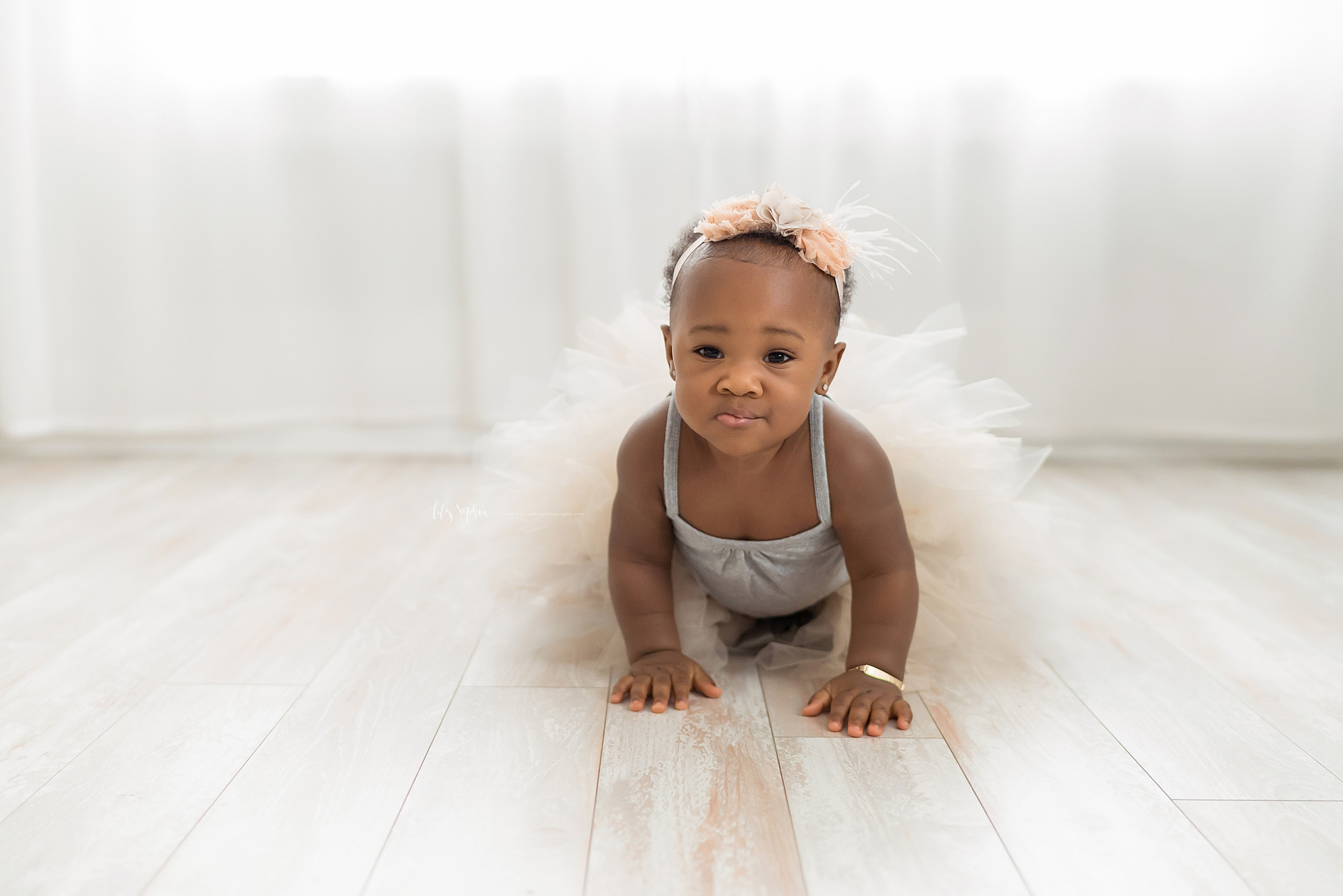 Milestone photo of an African-American little girl crawling on the floor of a natural light Atlanta studio in a tutu and wearing a cream headband adorned with peach roses.
