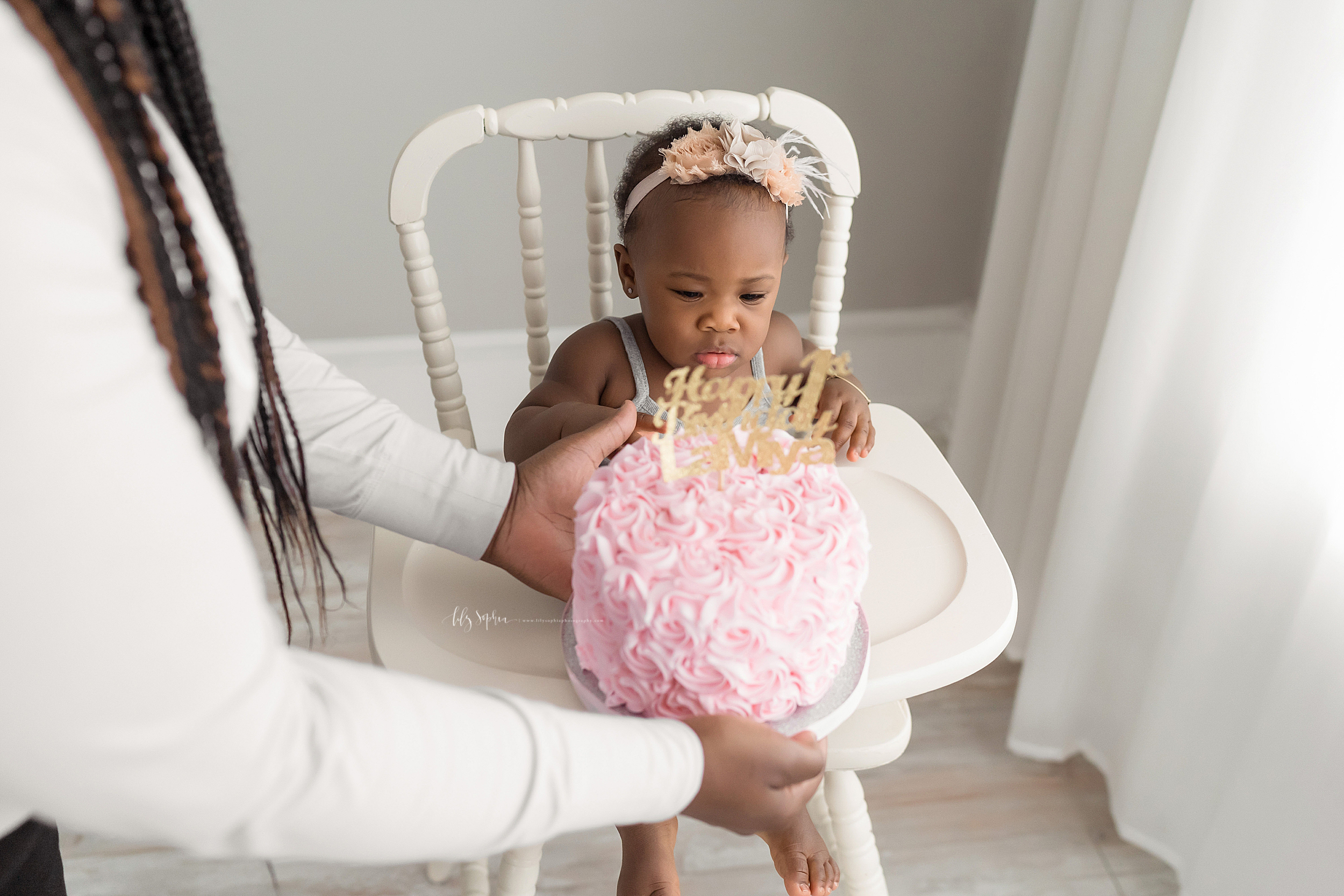 Milestone photo of a baby girl who is African-American as she sits in an antique high chair in natural light and sees her first birthday cake placed in front of her in a studio in Atlanta.