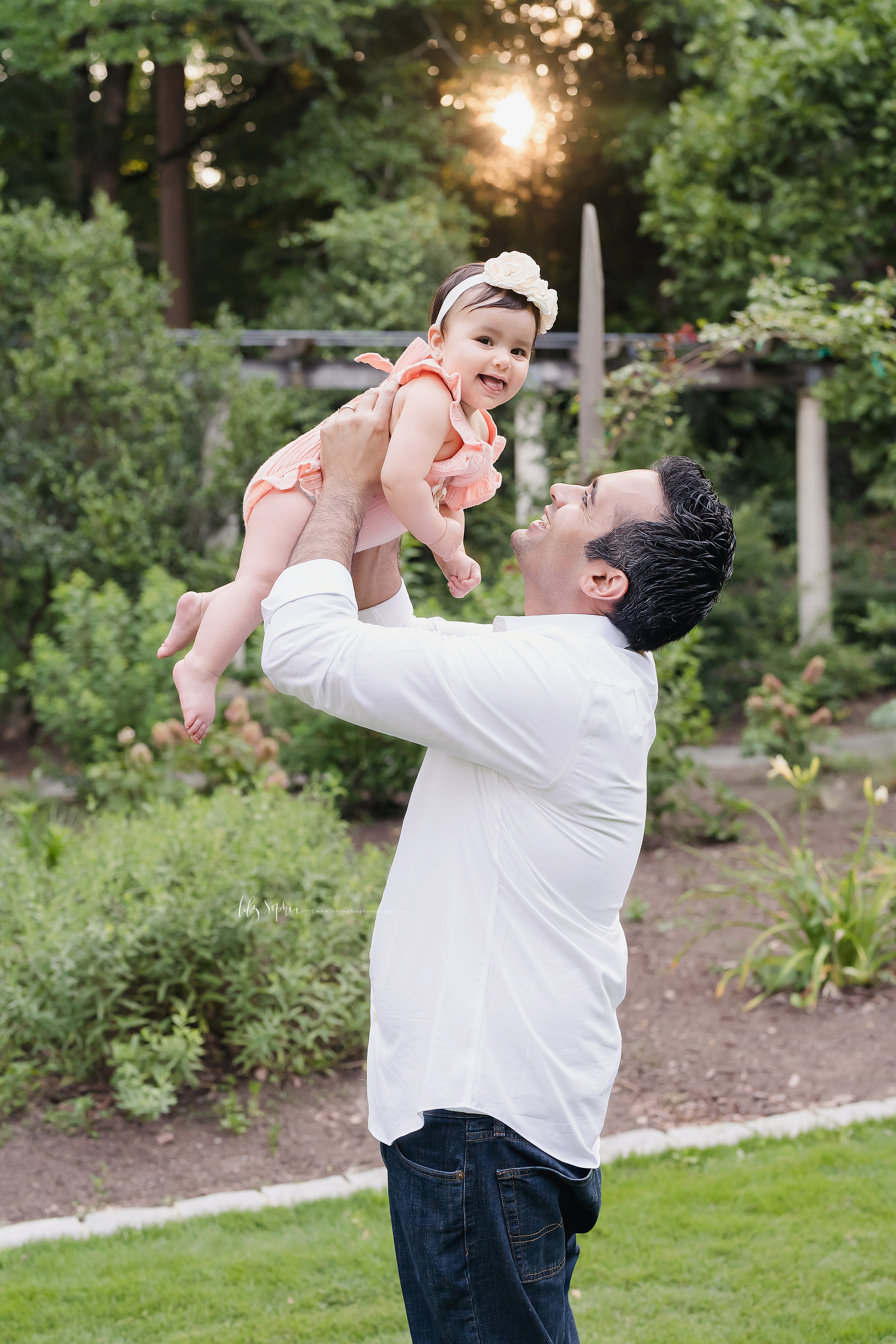 Photo of a dad and his daughter at sunset as he holds his daughter over his head in a garden in Atlanta.