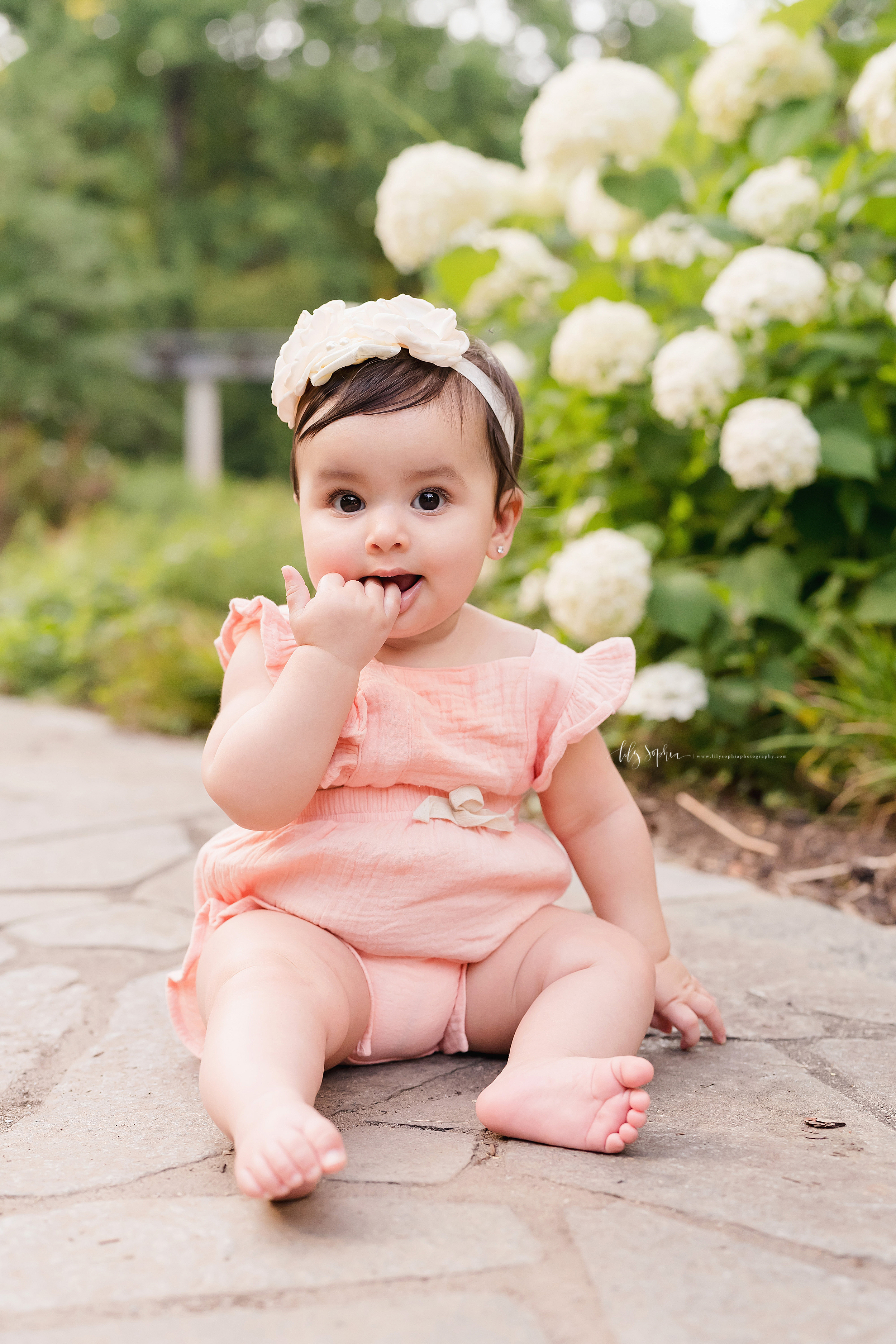 Milestone photo of a baby girl as she sits on a flagstone path and chews on her fingers in an Atlanta garden at sunset.