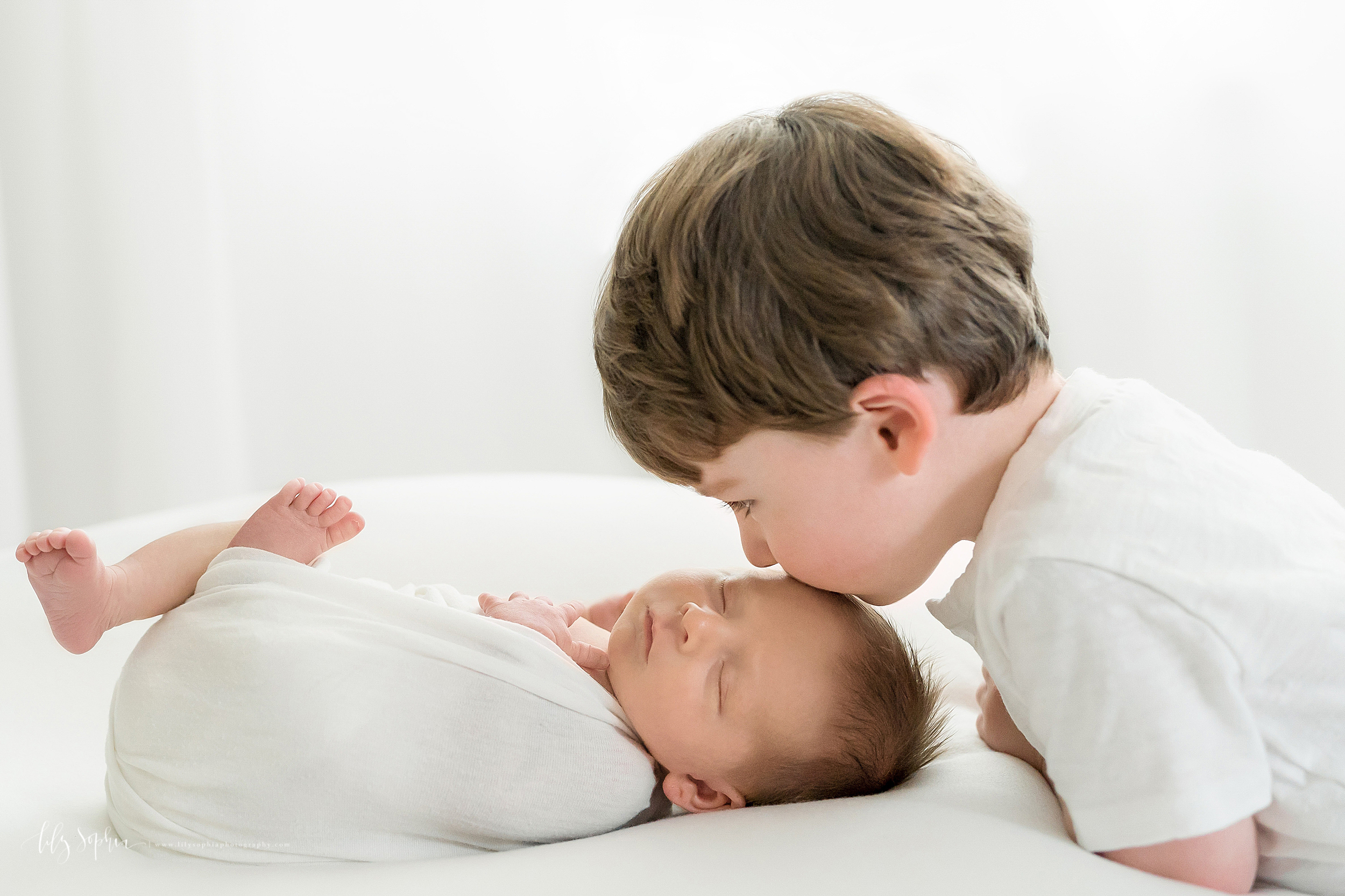 Newborn photo of a sleeping baby boy and his big brother as his brother kisses him on his head in Atlanta in natural light.