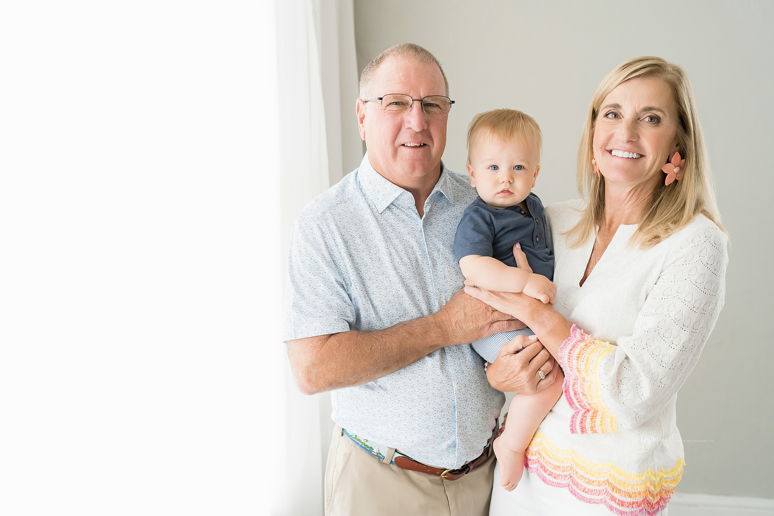 Family photo of grandparents with their grandson taken in Atlanta in a natural light studio.