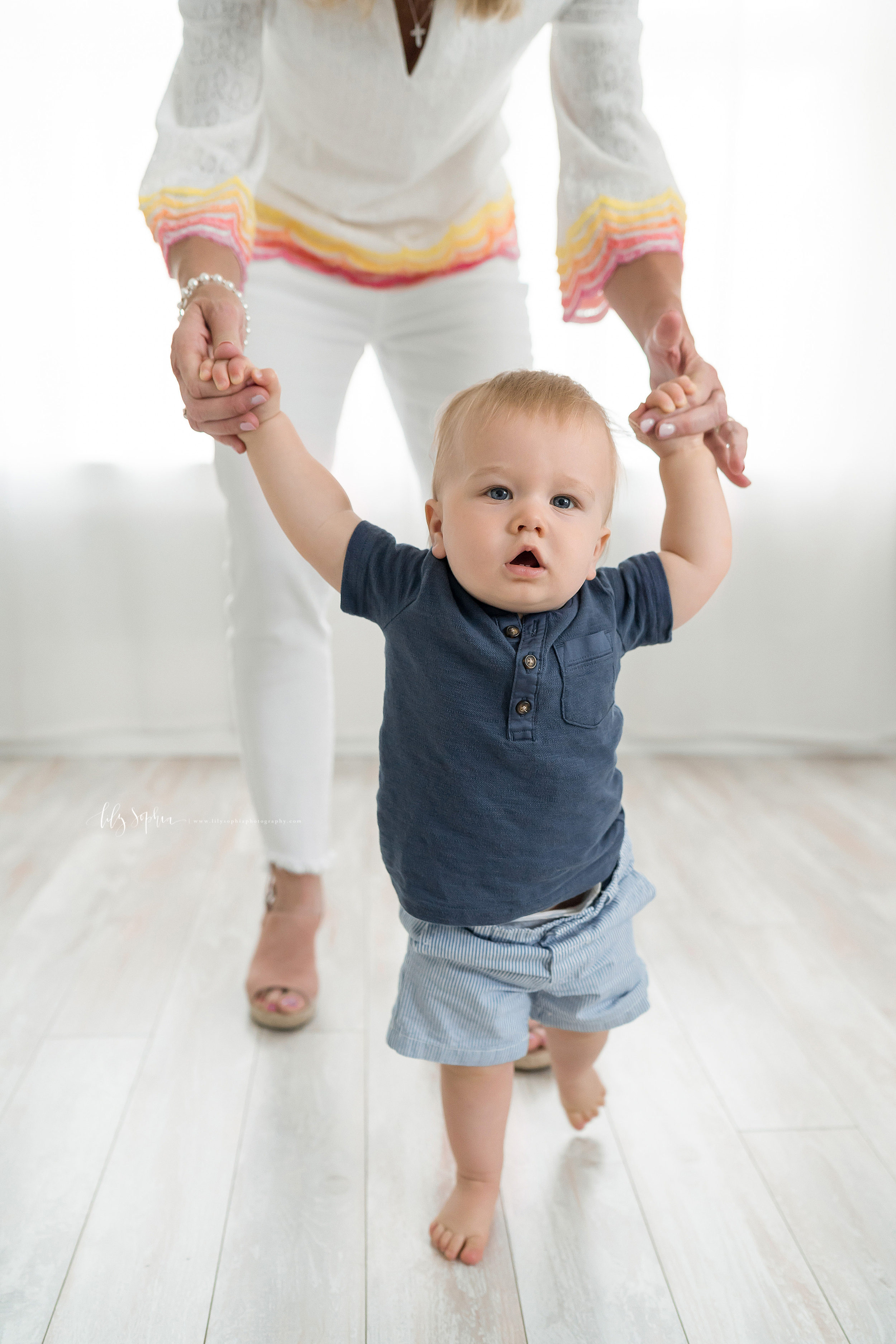 Milestone photo of an eager one year old taking steps while holding his grandmother's hands in a studio in Atlanta in natural light.