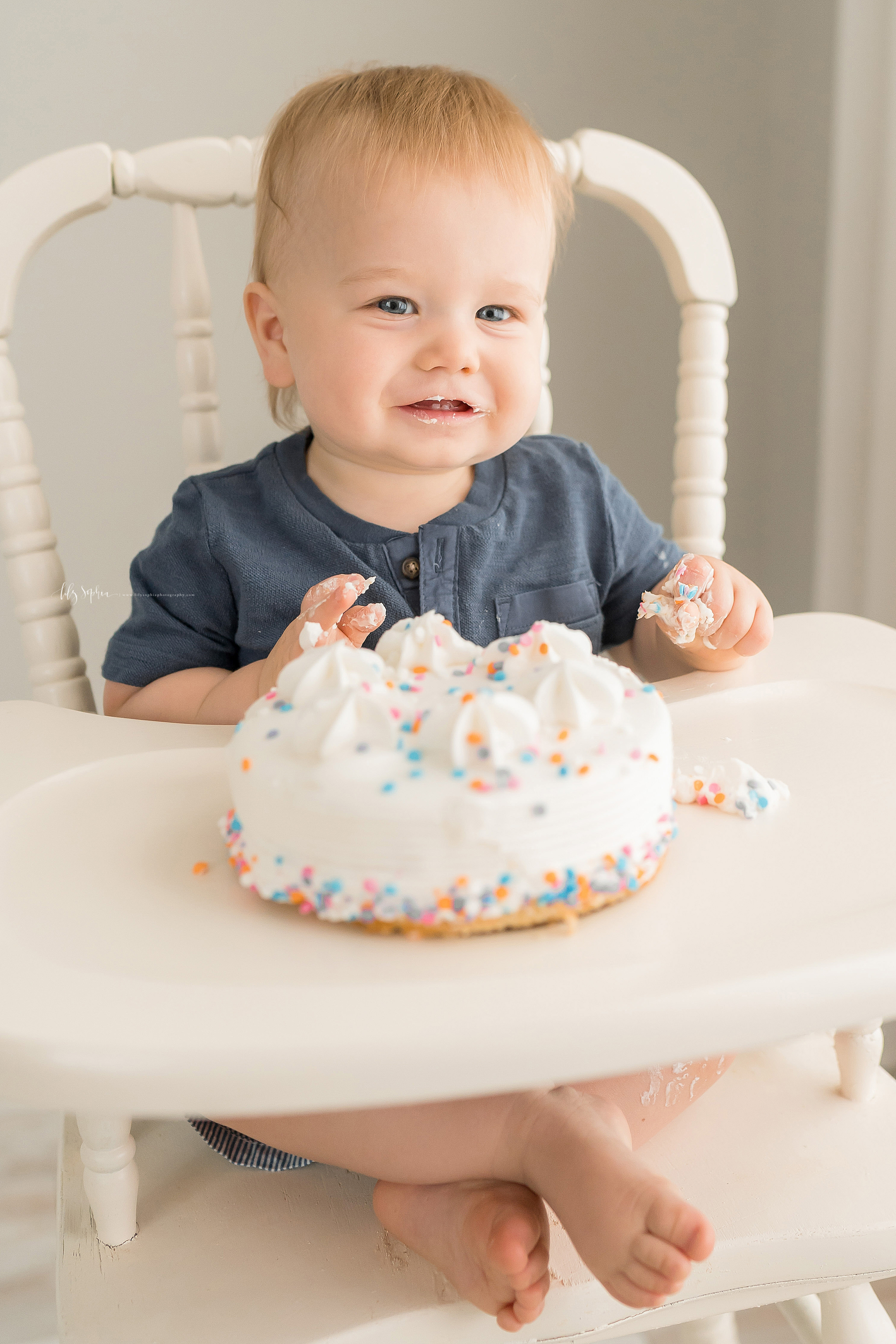 Milestone photo of a baby boy with icing on his hands in a natural light studio as he samples his first birthday cake while sitting in an antique highchair in Atlanta.