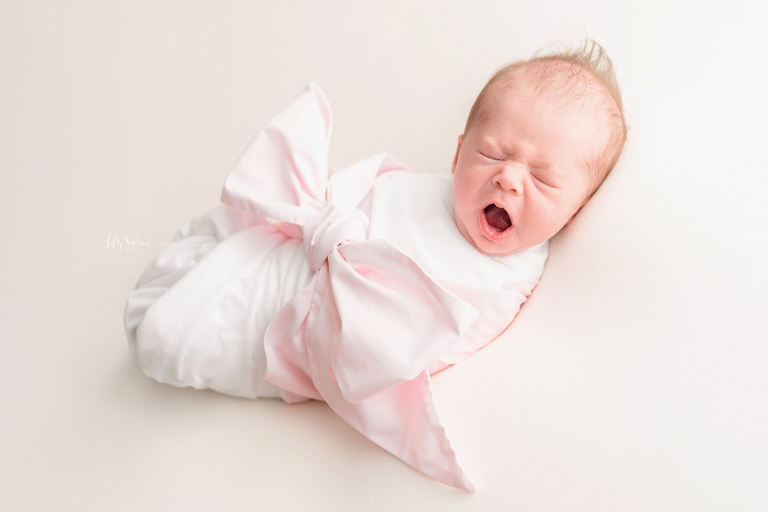 Photo of a newborn bundle of joy as the baby girl who is swaddled to her chin and wrapped in a large pink bow yawns in a natural light studio in Grant Park, Georgia.