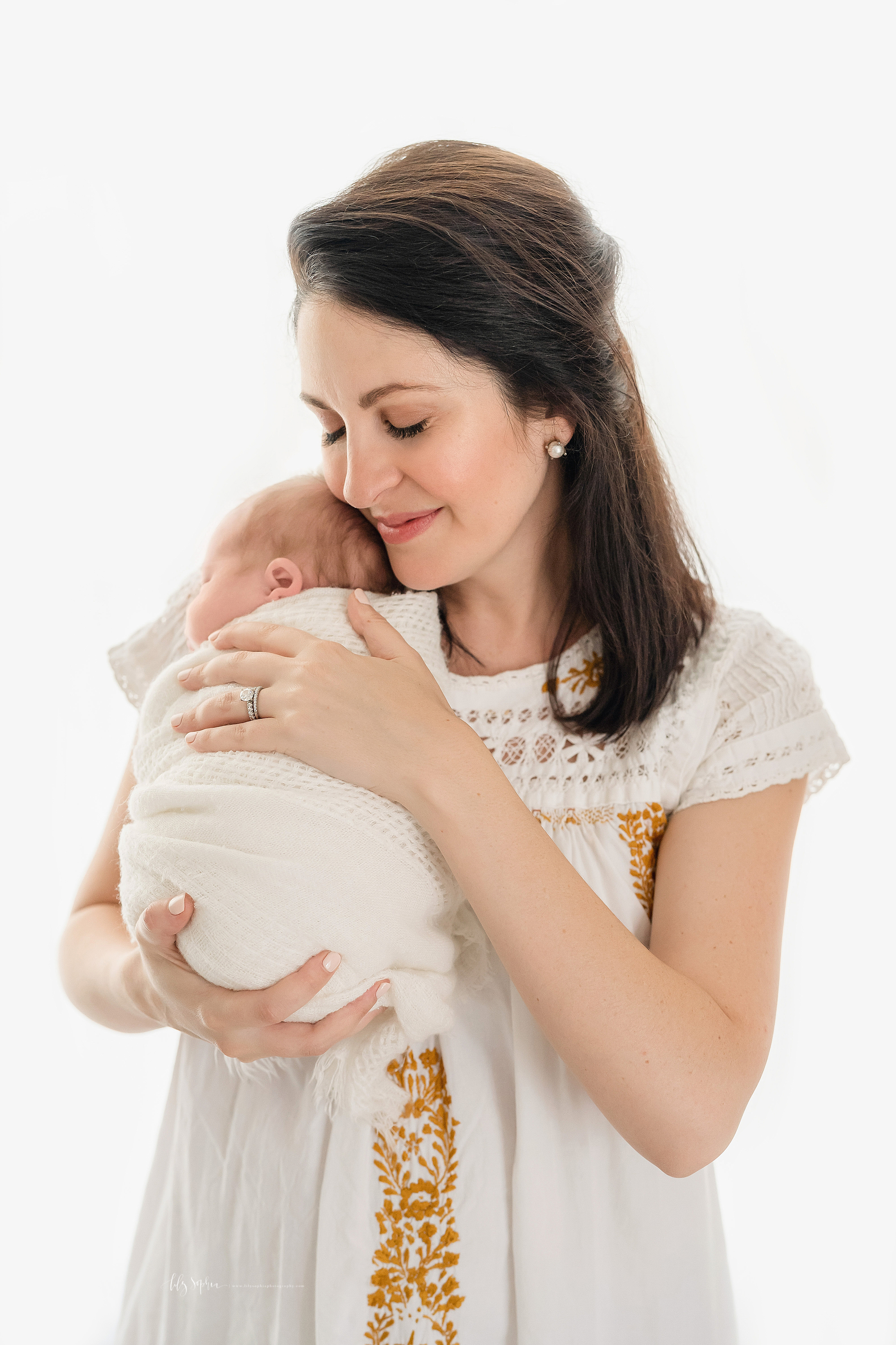 Photo of a contented mom and her sleeping newborn baby girl in natural light in an Atlanta studio.