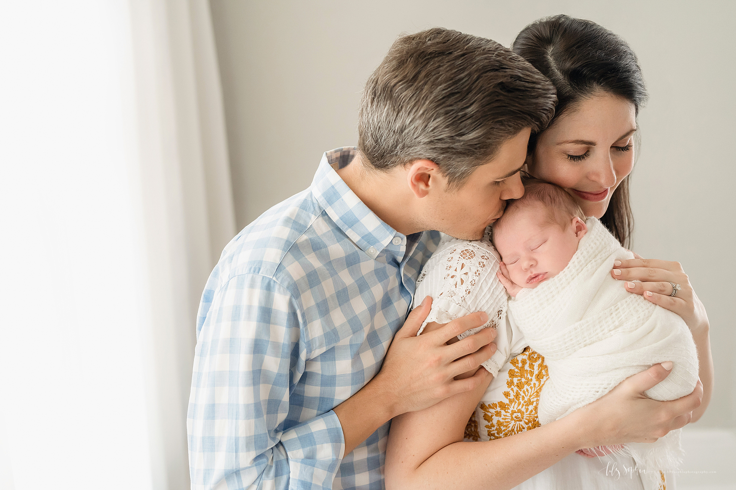 Family photo of a mom and dad snuggling with their contented newborn daughter as they stand in an Atlanta studio holding her.