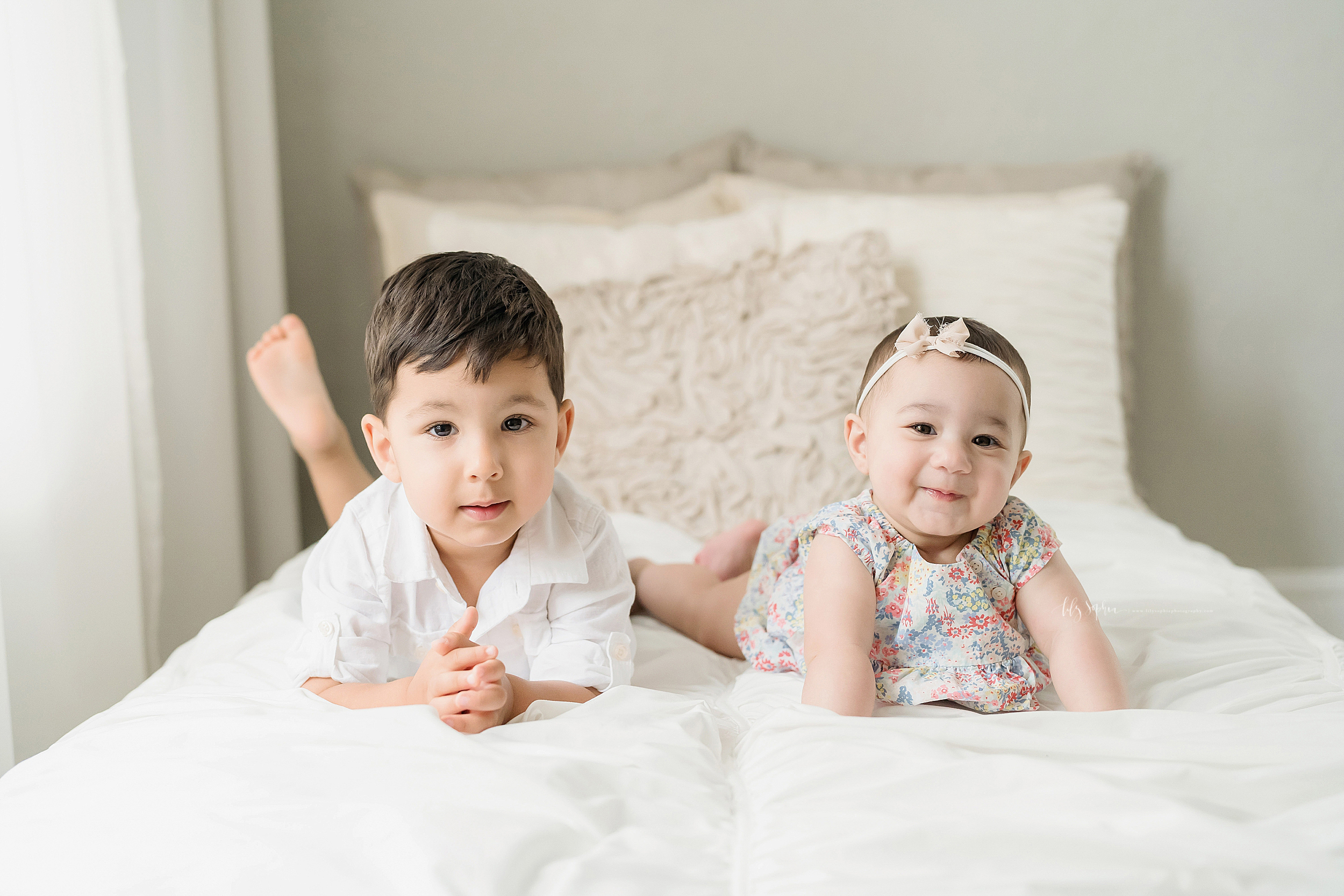 Photo of siblings, a brother and a sister,  hanging out on a bed in a natural light Atlanta studio.