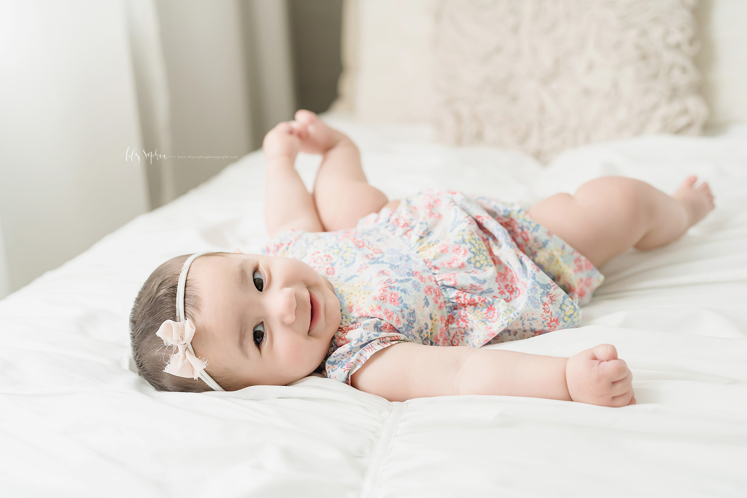 Photo of a smiling six month old as she plays with her toes while lying on a bed in an Atlanta natural light studio.