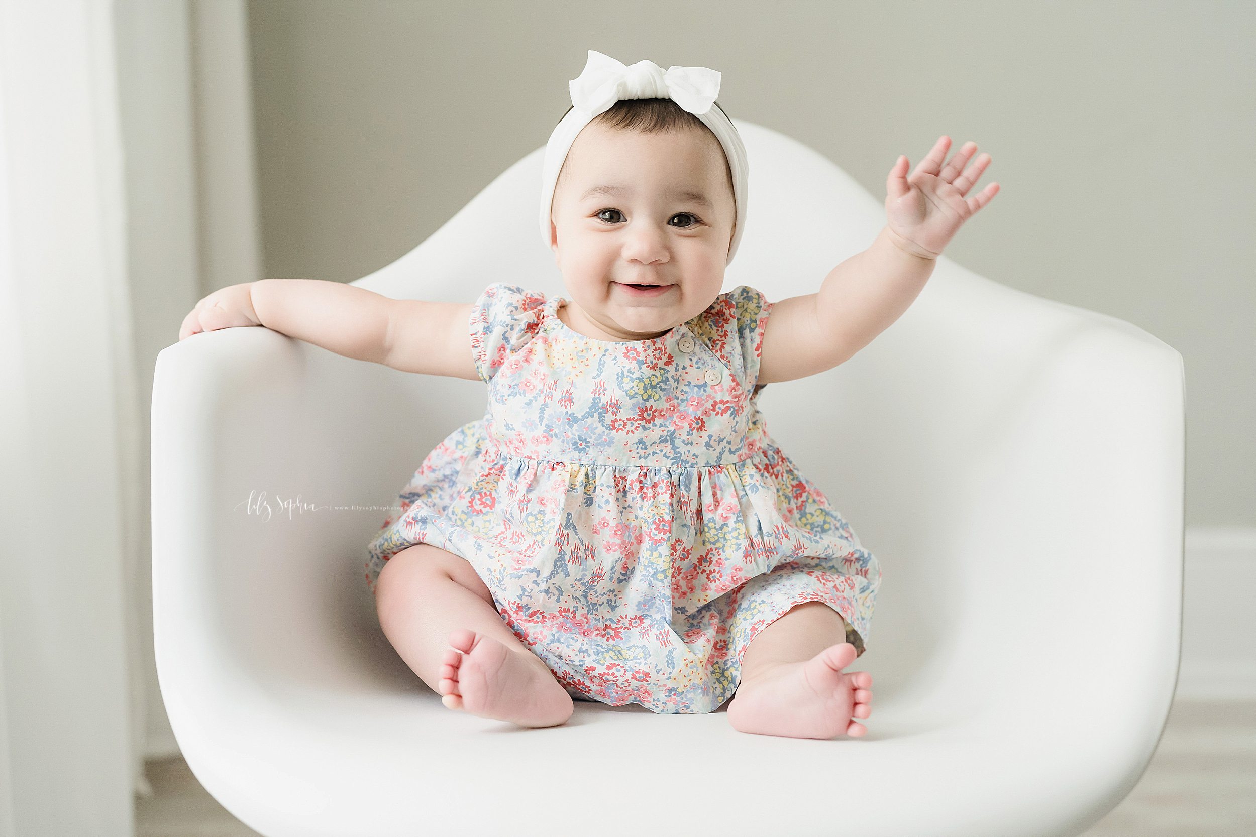 Milestone photo of a six month old little girl in a natural light studio as she sits in a white molded chair and waves hello in Atlanta.