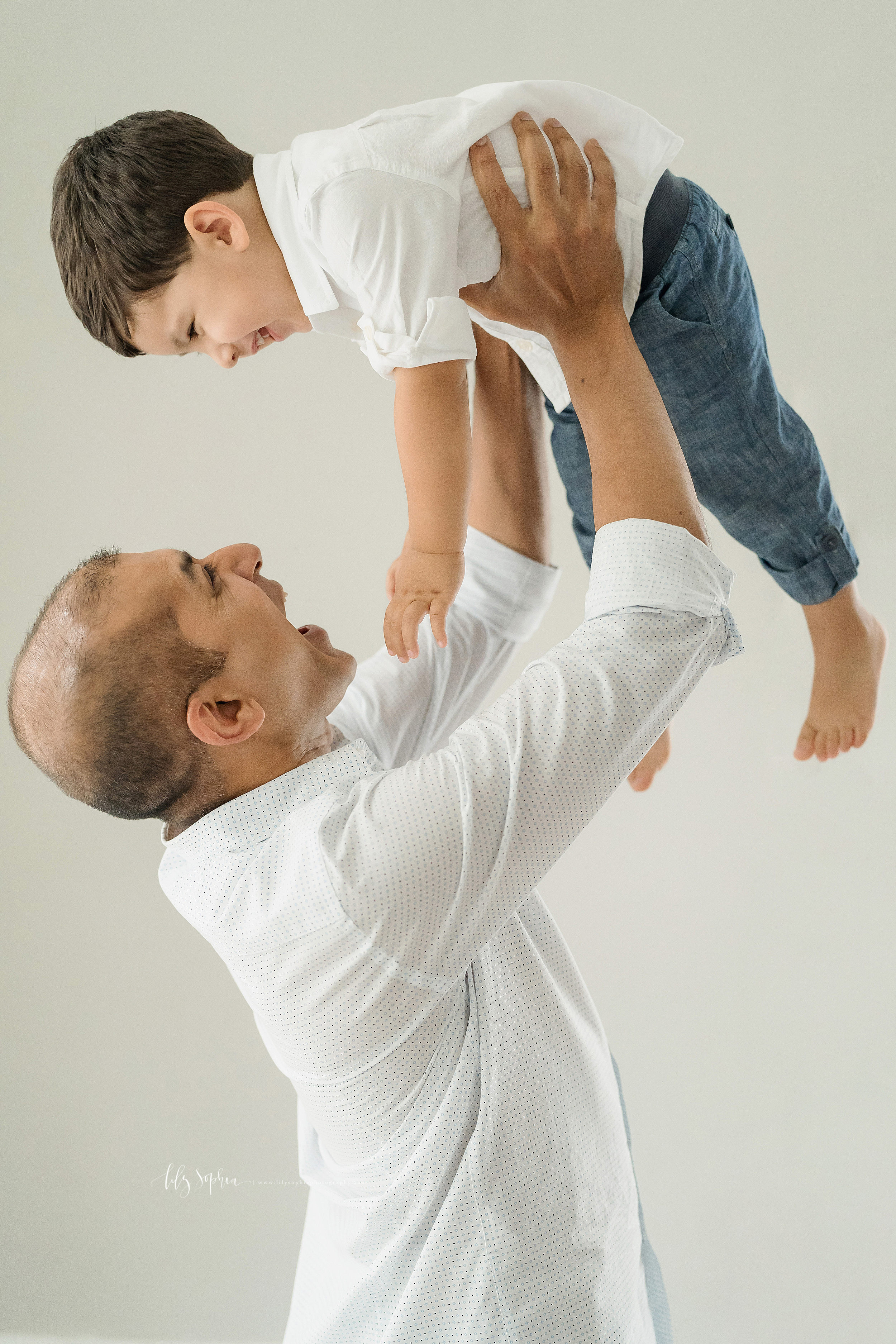 Family photo of a father lifting his son above his head as the two laugh together in an Atlanta studio.