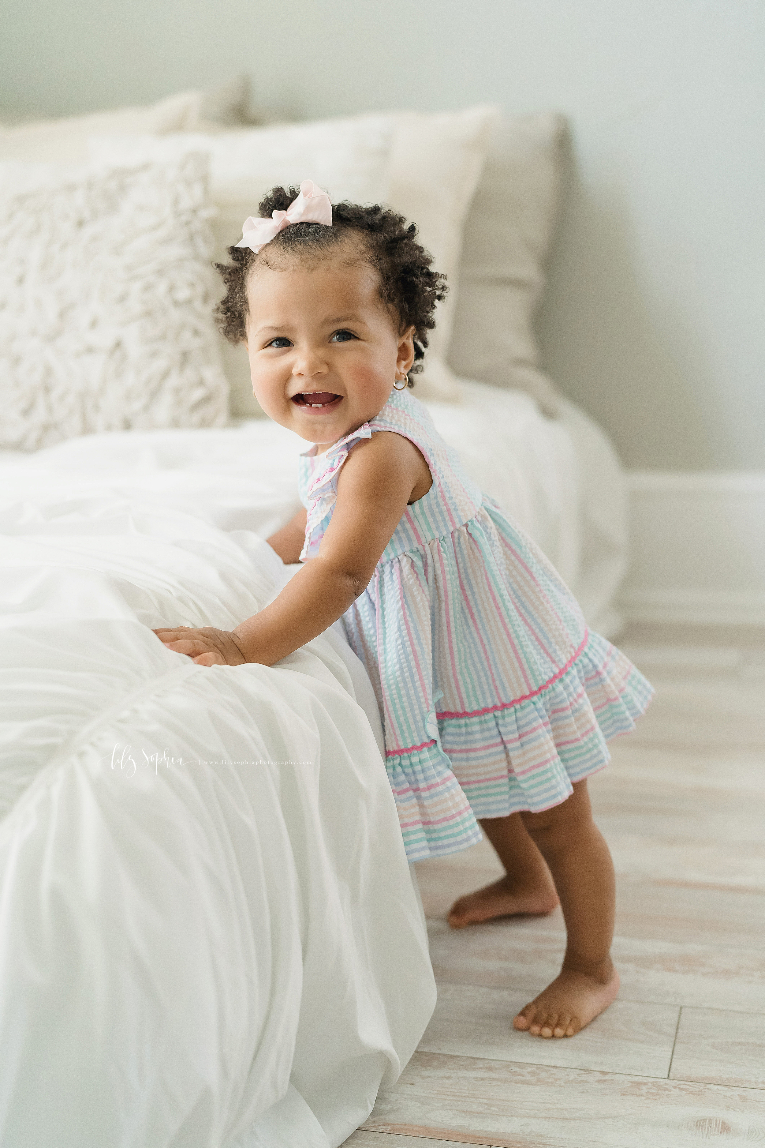 Milestone photo of a proud one year old African American girl standing next to a bed in natural light in an Atlanta studio.