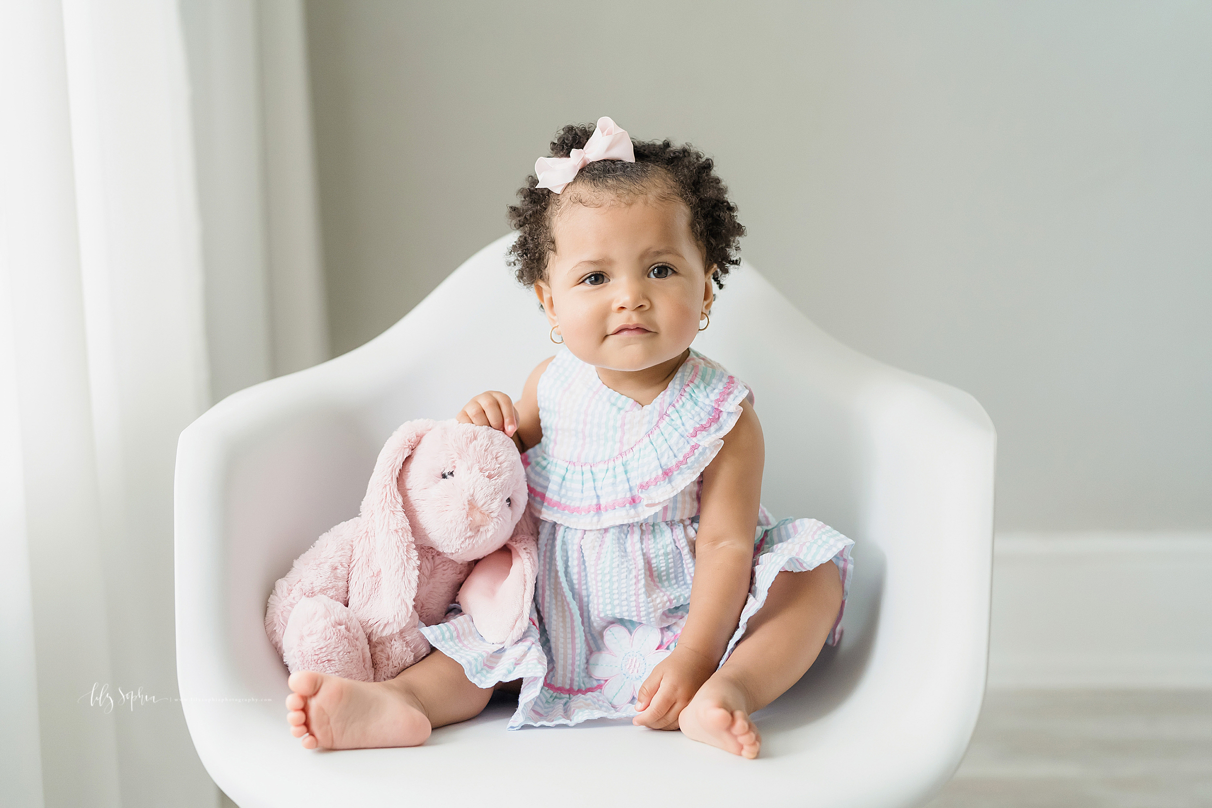 Milestone photo of an African-American one year old with her pink floppy eared bunny sitting in natural light in a white molded chair in an Atlanta studio.