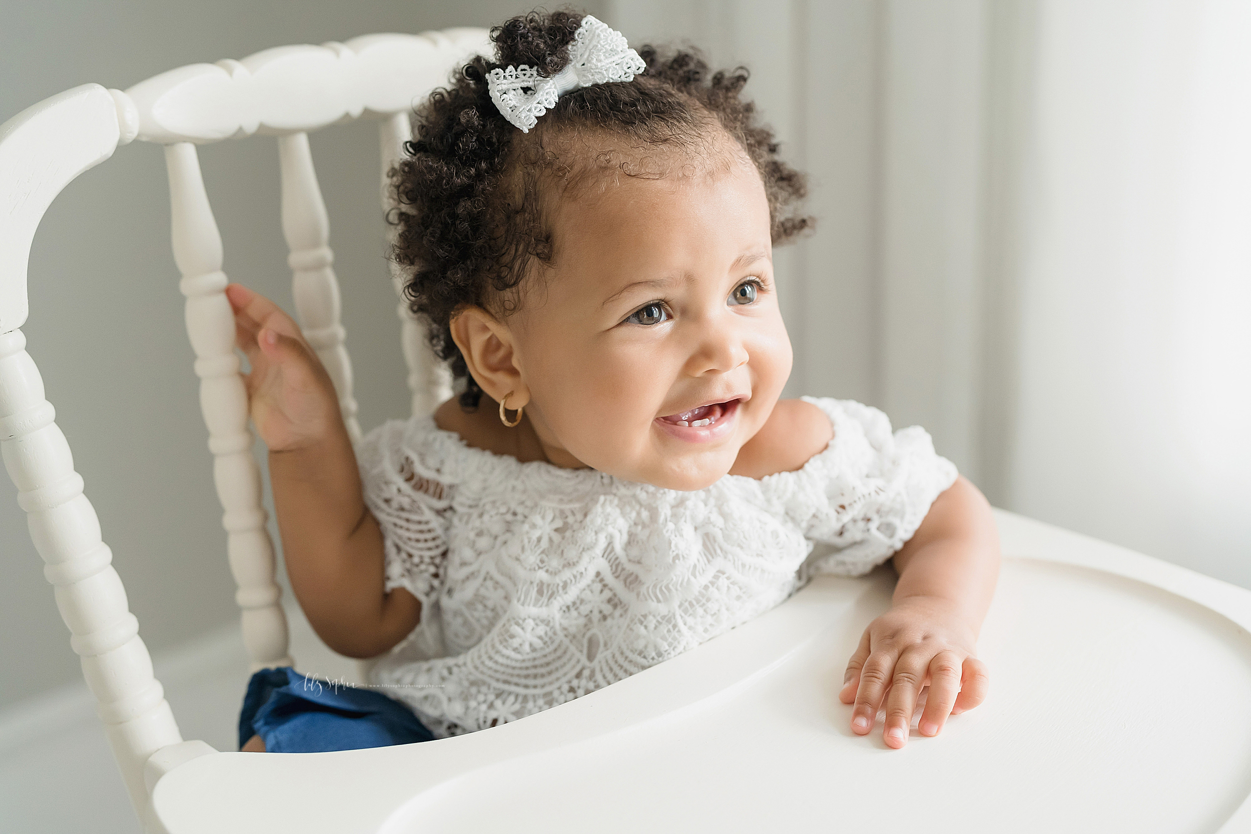 Milestone photo of a one year old girl who is African-American as she sits in an antique high chair in natural light in Atlanta.