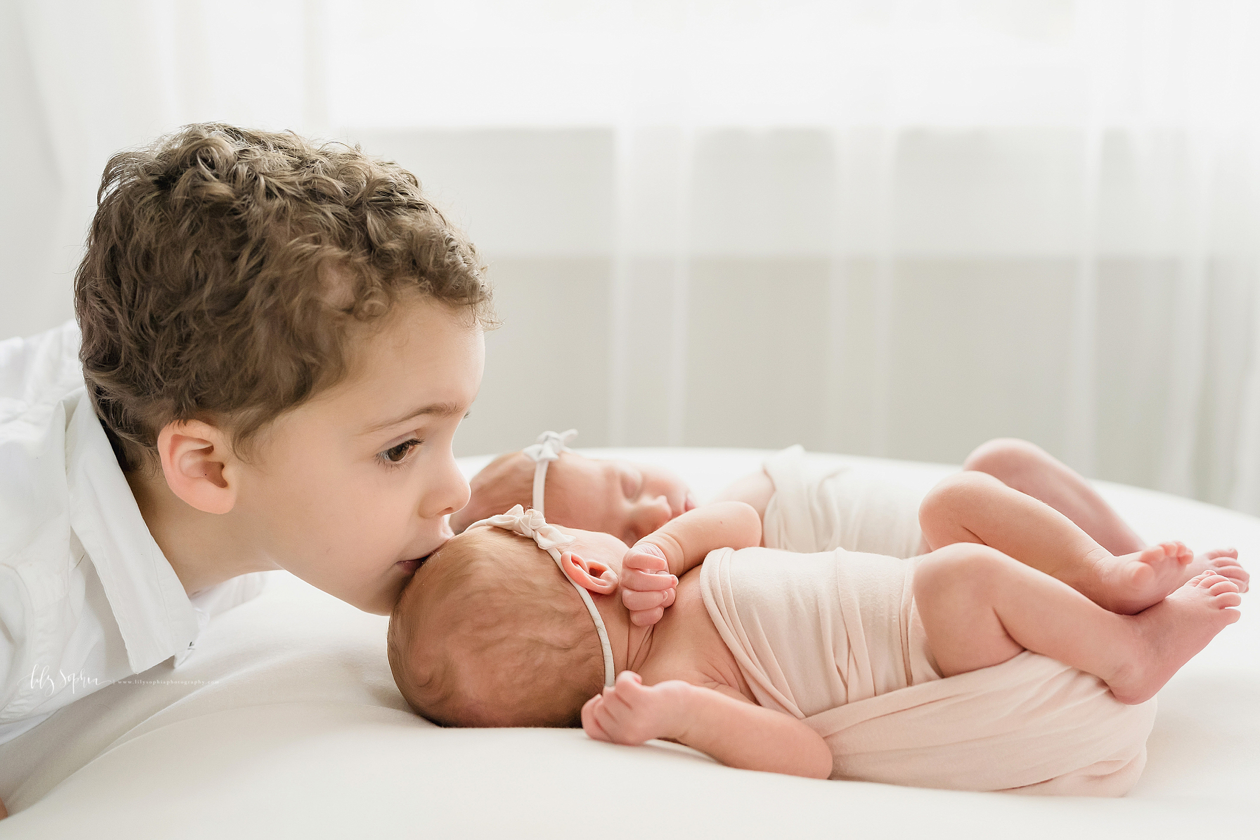 Family photo of a brother and his newborn twin siblings as he kisses the head of his sister while the twins lay on a bed in an Atlanta studio in natural light.