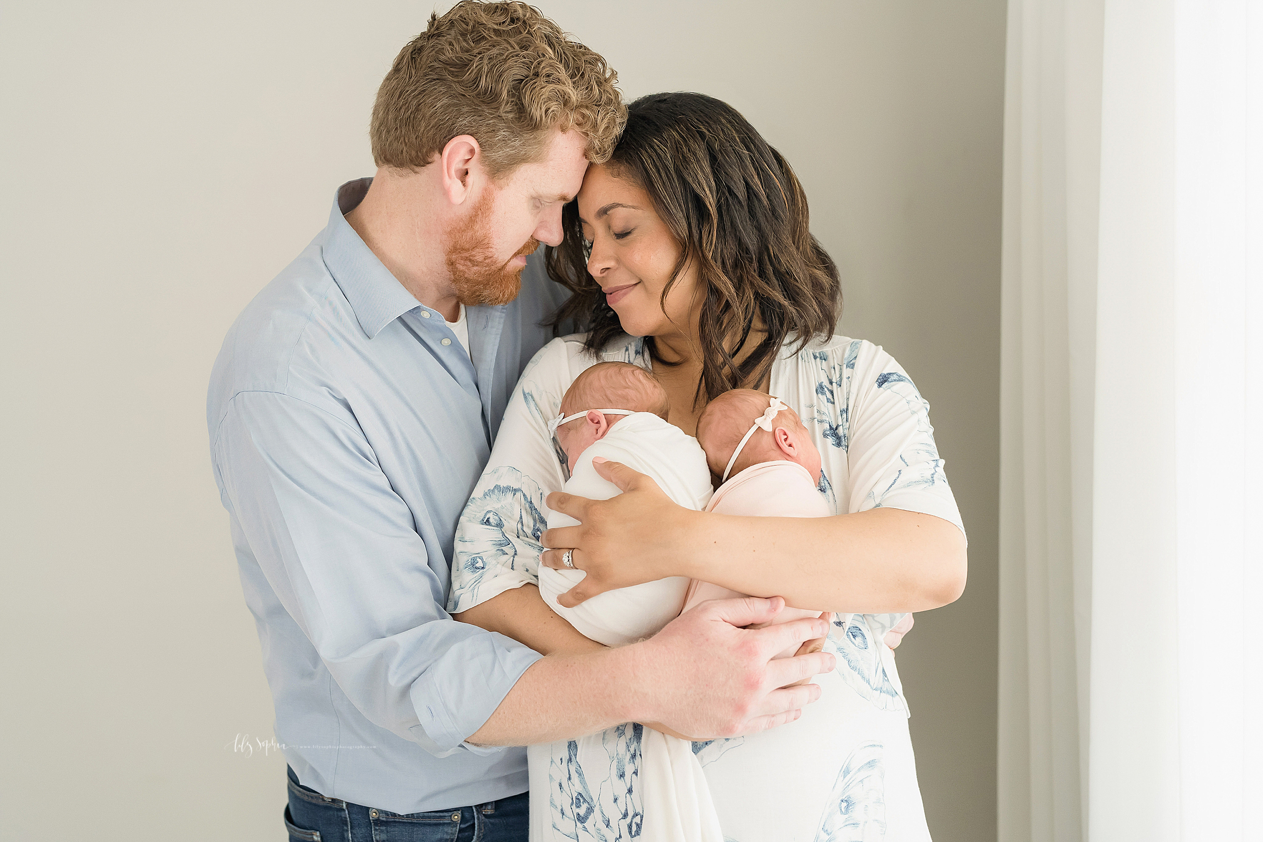 Family photo of a mother and father embracing one another with thankful looks on their faces as mom holds her newborn twins in her arms in a natural light Atlanta studio.