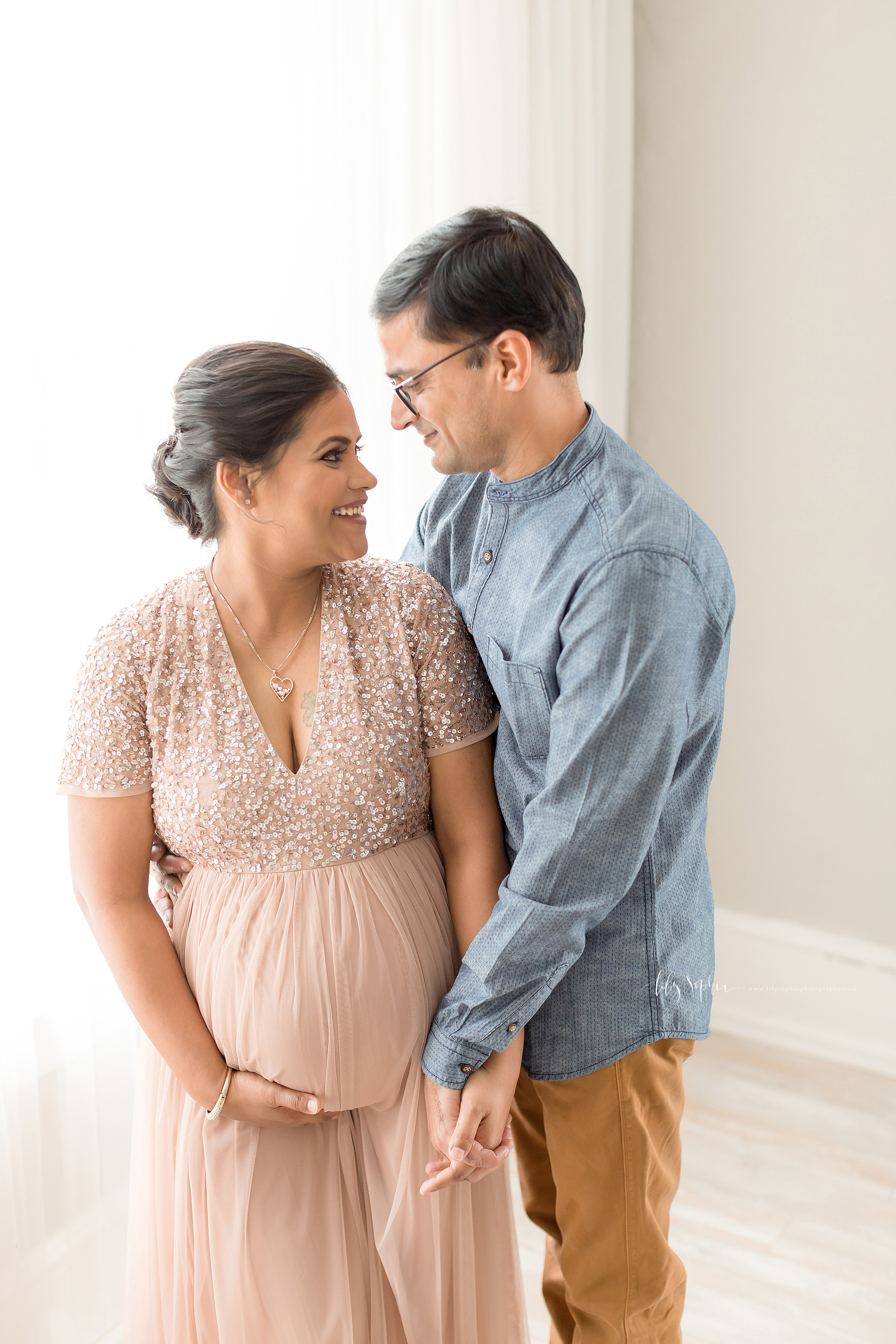 Maternity photo of an Indian husband and wife as they hold hands and smile at one another in a natural light Atlanta studio.