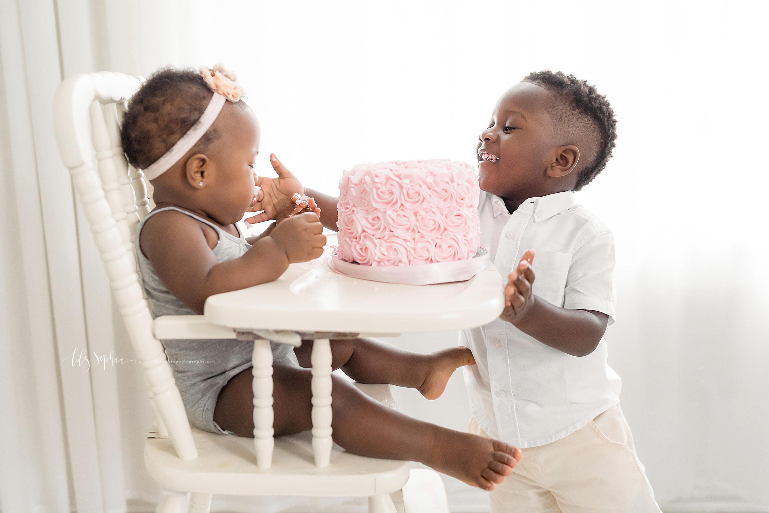 Family photo of an African-American brother helping his one year old sister taste the icing of her birthday cake as she sits in an antique high chair in an Atlanta natural light studio.