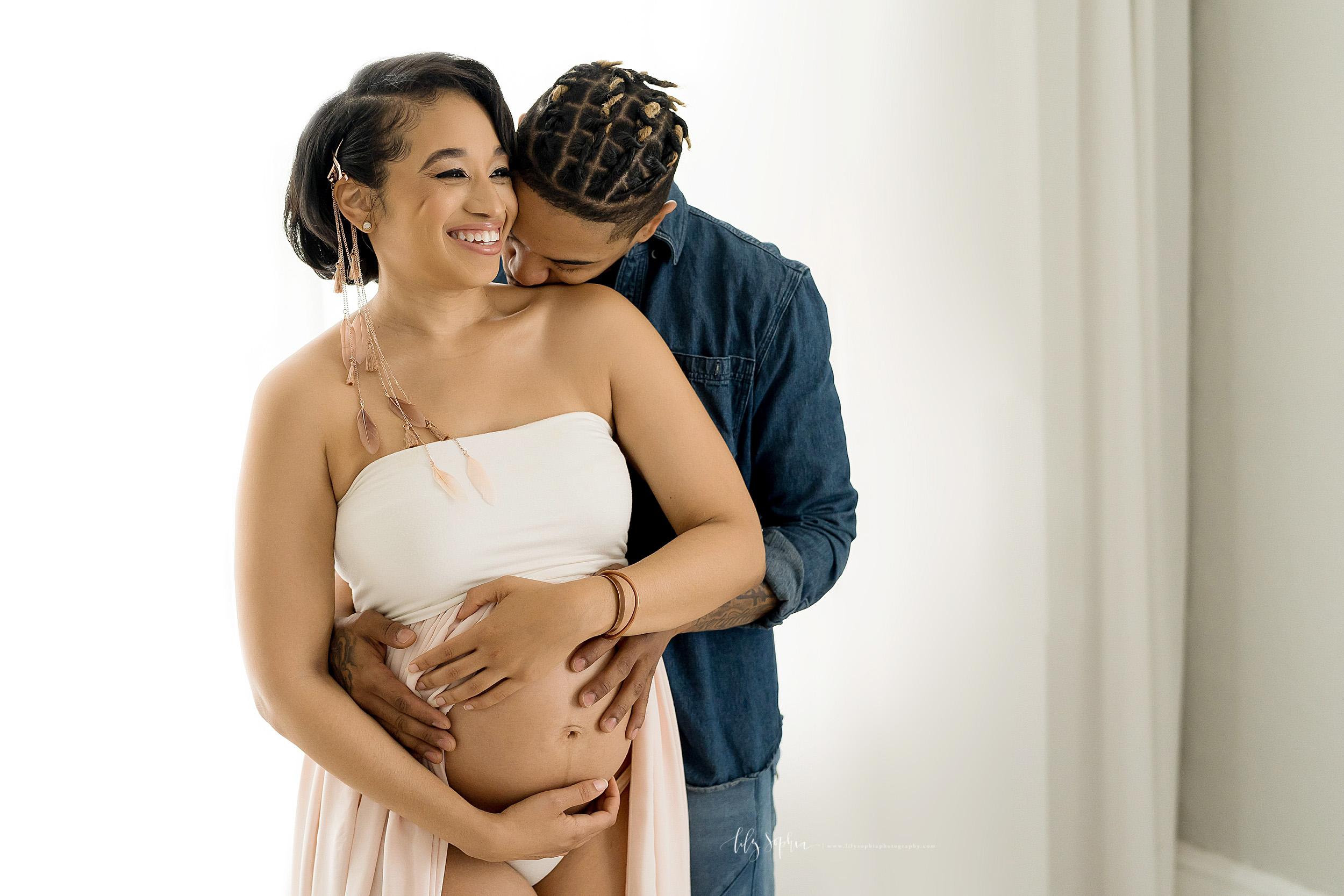 Smiling pregnant African-American woman stands in a bandeau split-front gown as her husband kisses her on her shoulder and the two of them embrace her bare pregnant belly in an Atlanta studio using natural light photography.